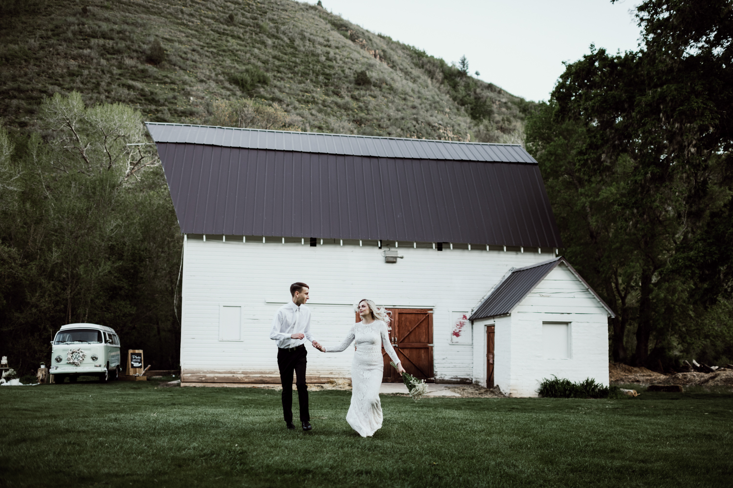 bride and groom running in front of white barn
