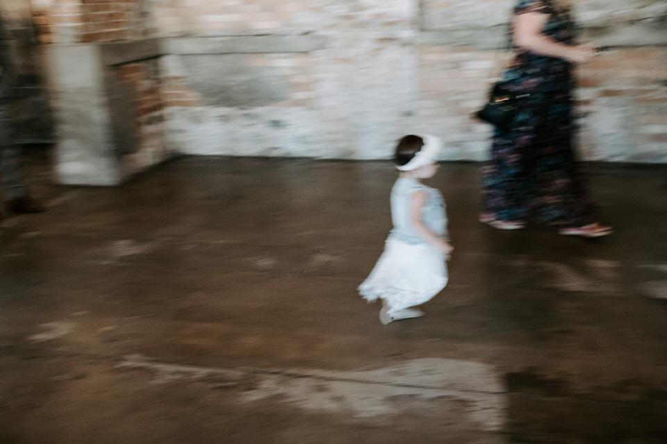 motion blur of little girl running at wedding