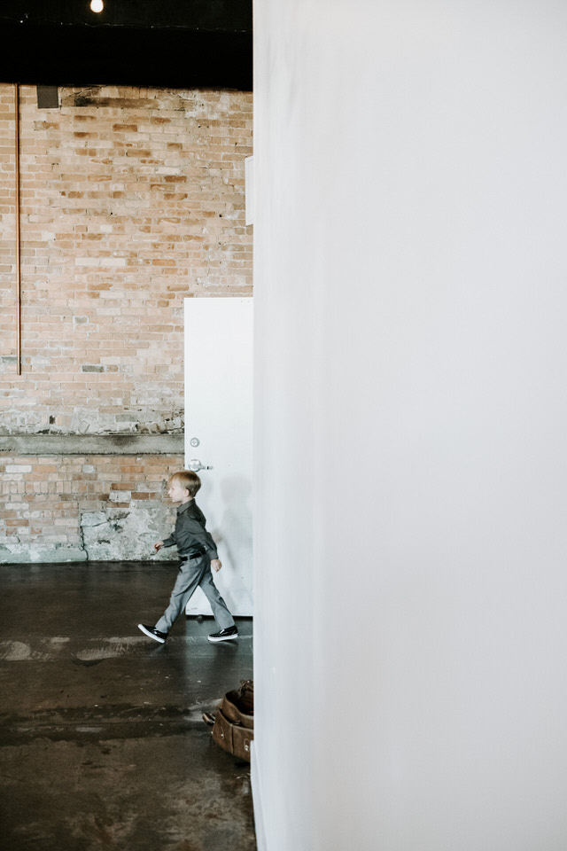 little boy walking in industrial wedding venue