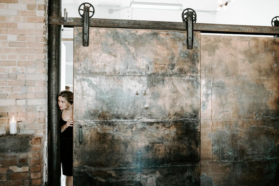 girl looking through industrial sliding door at wedding