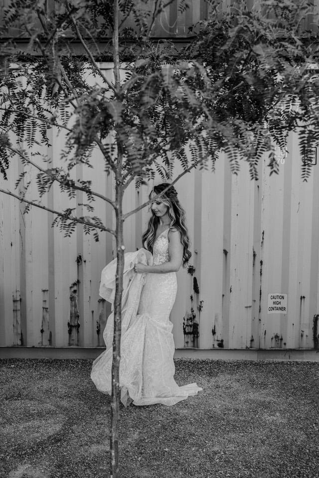 bride standing behind tree at wedding