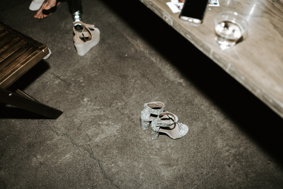 rhinestone shoes on the floor at a wedding reception