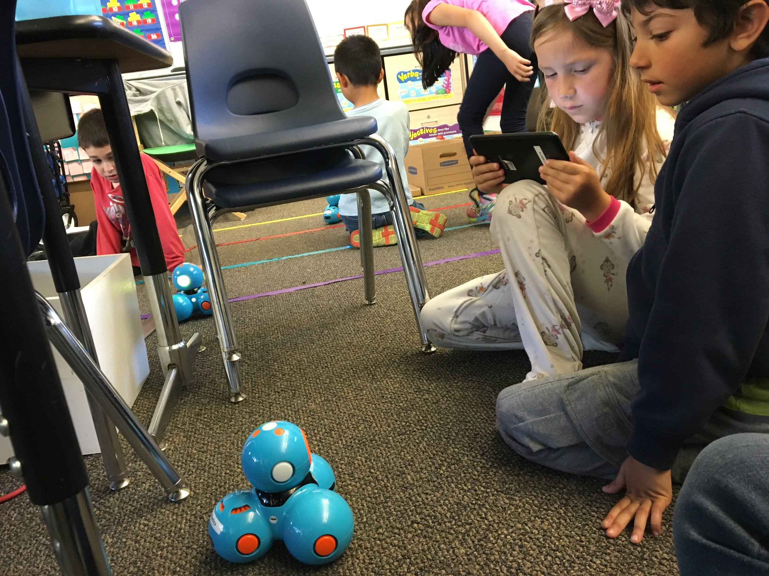 Students working to code a robot through a challenge
