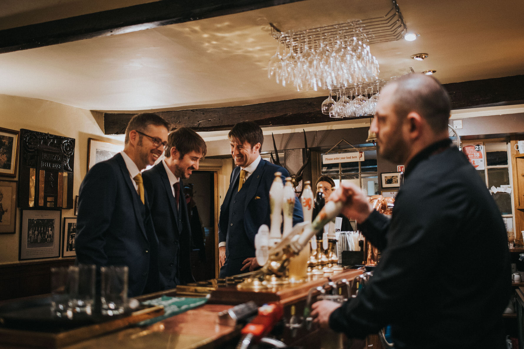 Candid unposed documentary wedding photography by Louise Jacob - Image of groom and groomsmen at the bar