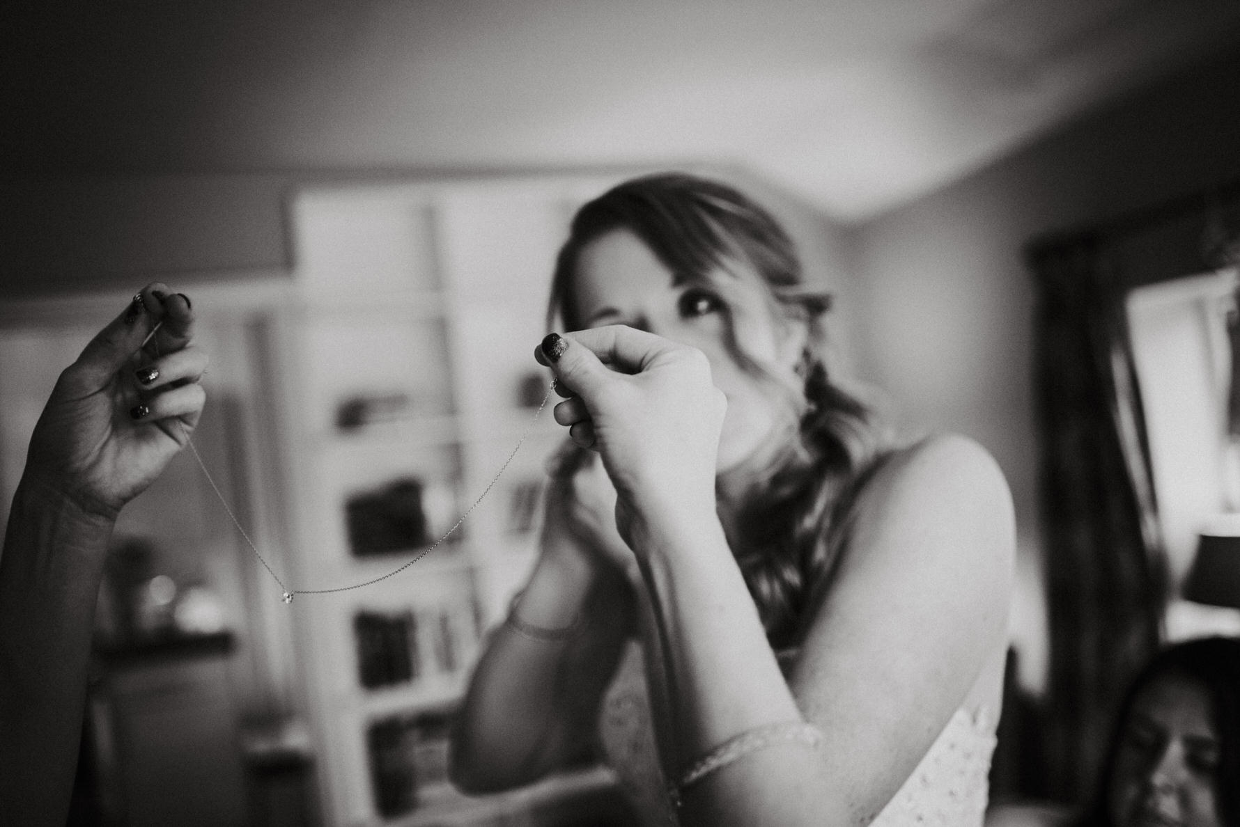 Cheshire documentary wedding photography by Louise Jacob - A bridesmaid putting on the brides necklace