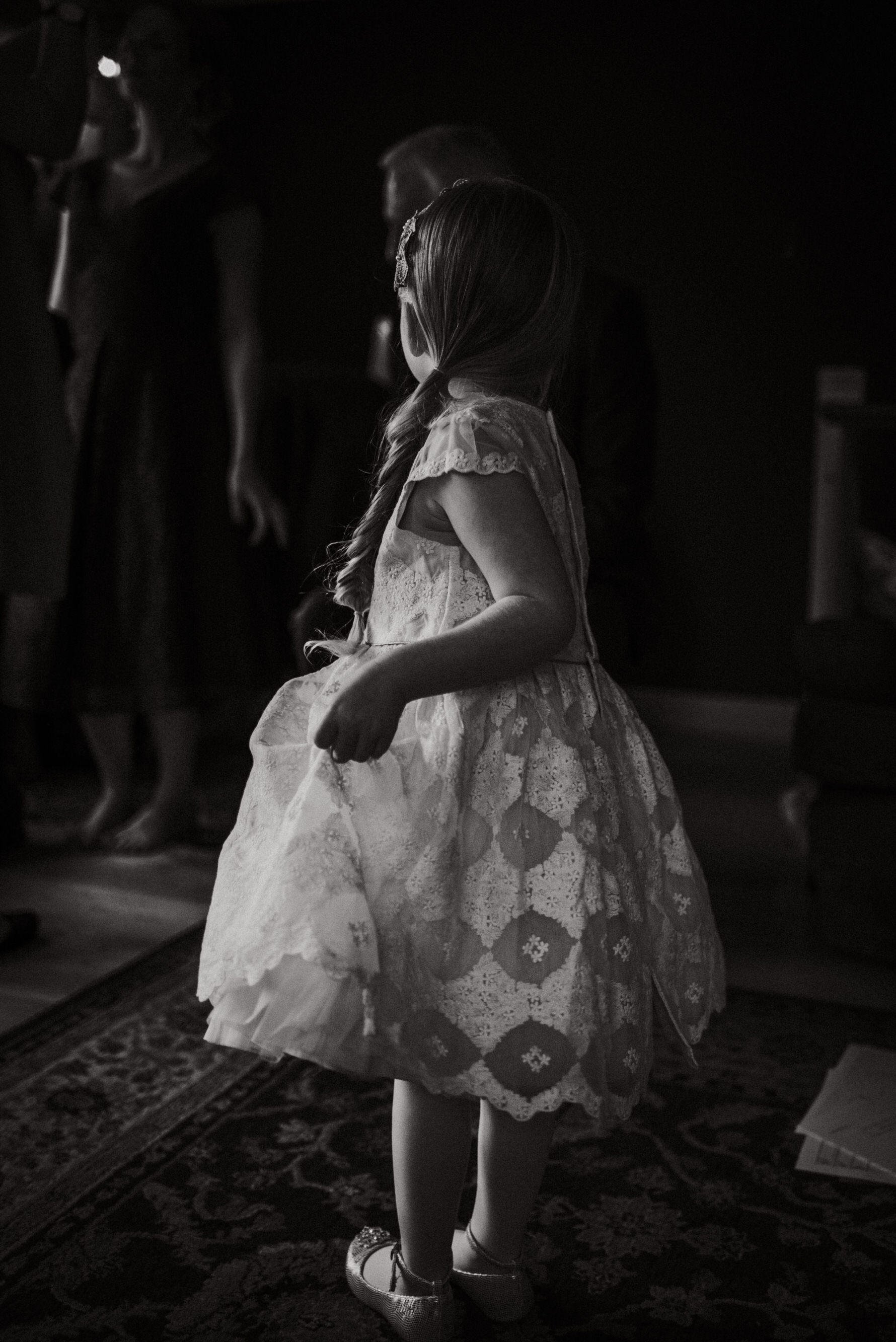A black and white image of a flower Girl holding her dress