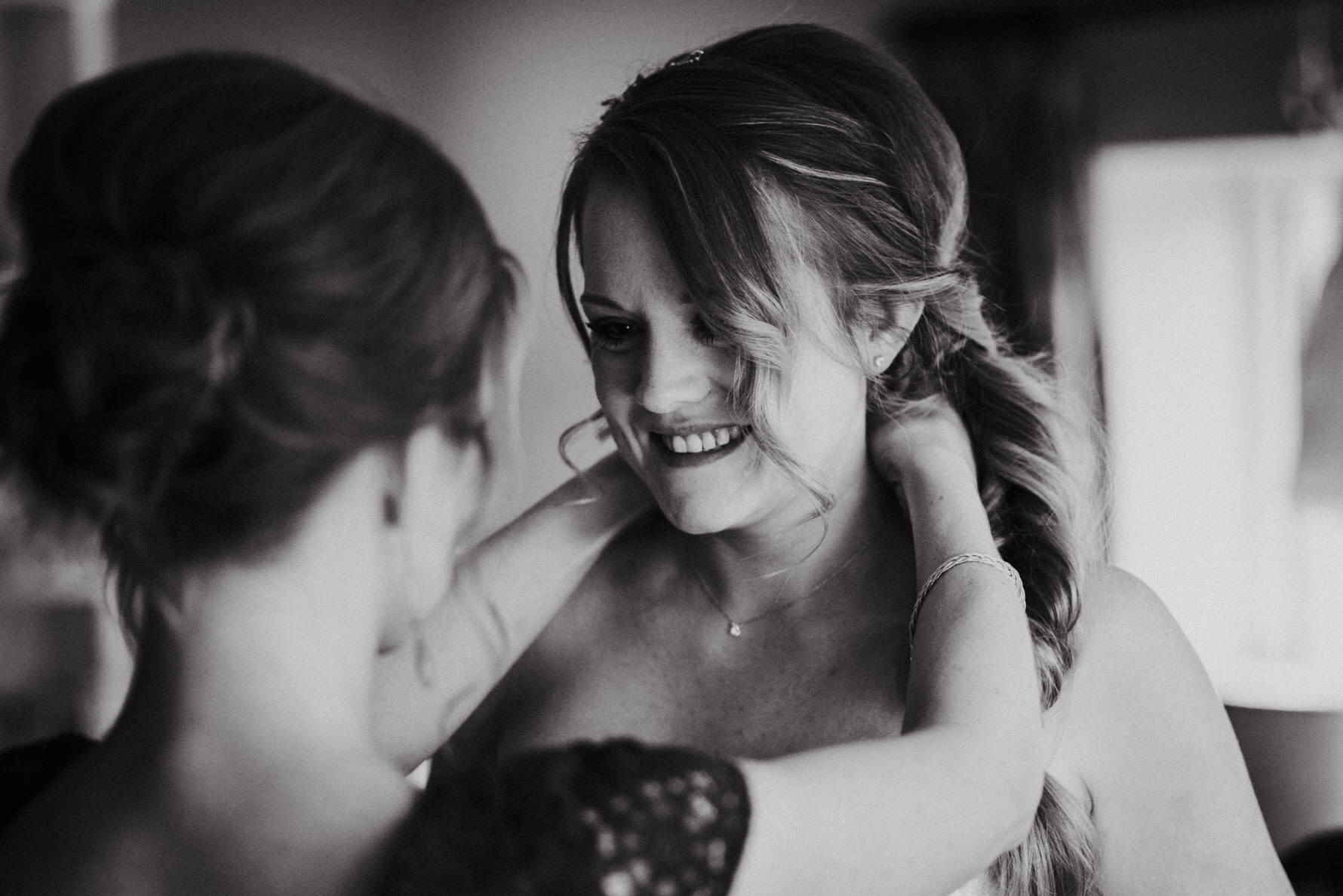 Documentary Wedding Photography - a bridesmaid helping the bride with her necklace