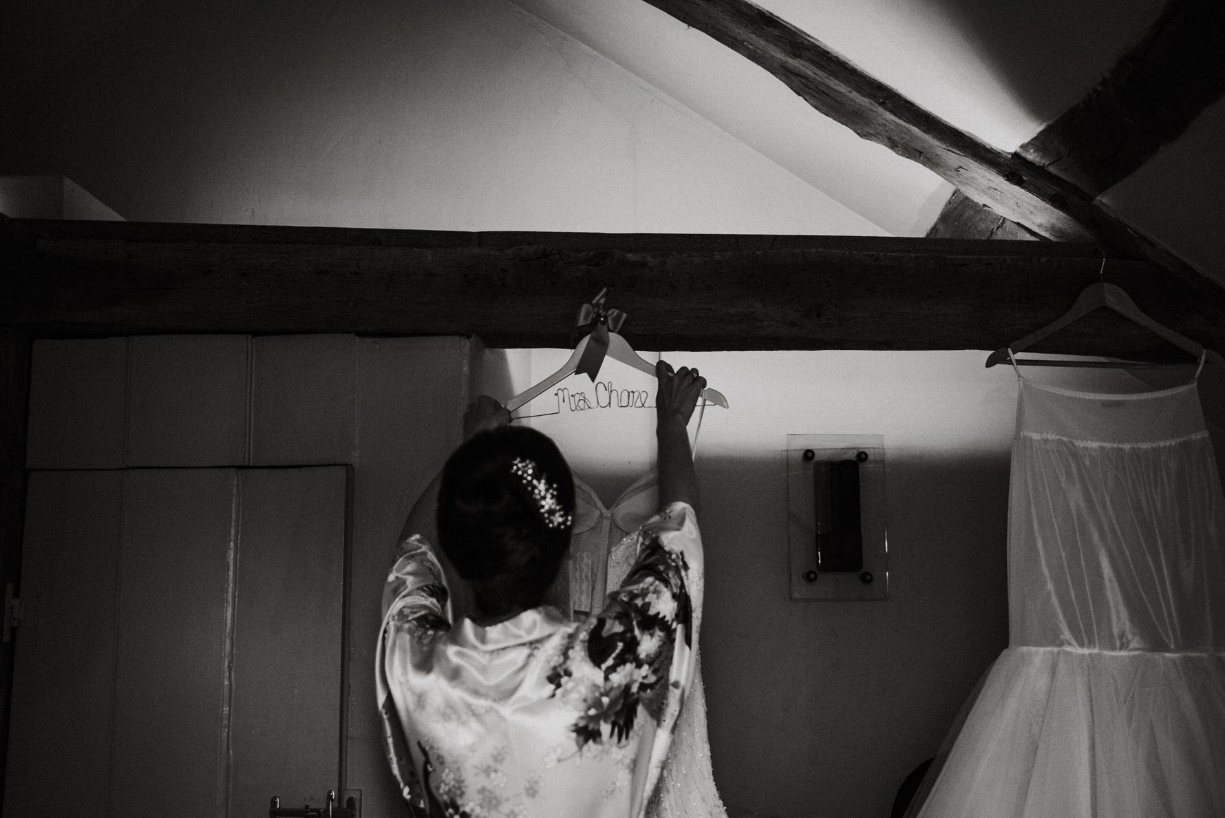 Wedding photojournalism - A bride reaching up for her wedding dress