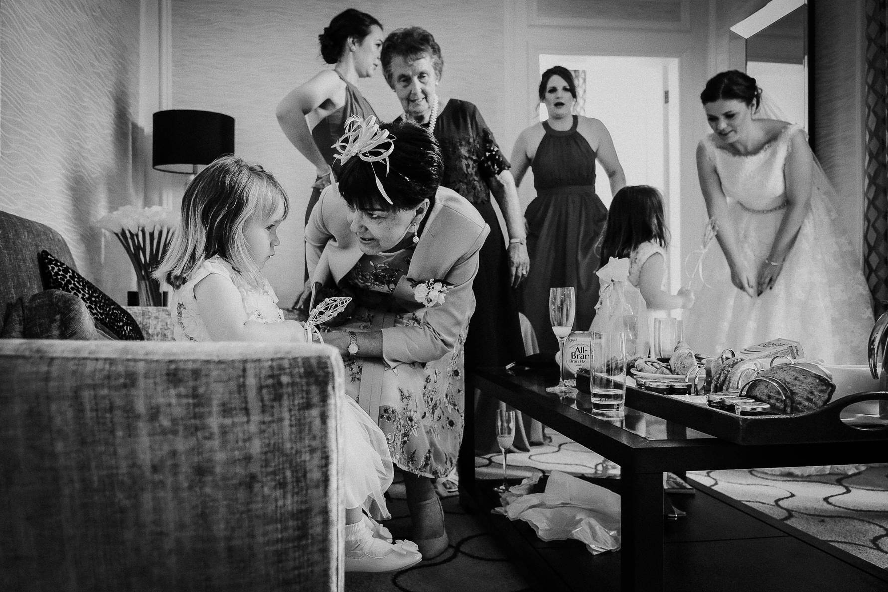 Wedding photojournalism - Mother of the bride and flower girl moment during busy bridal prep