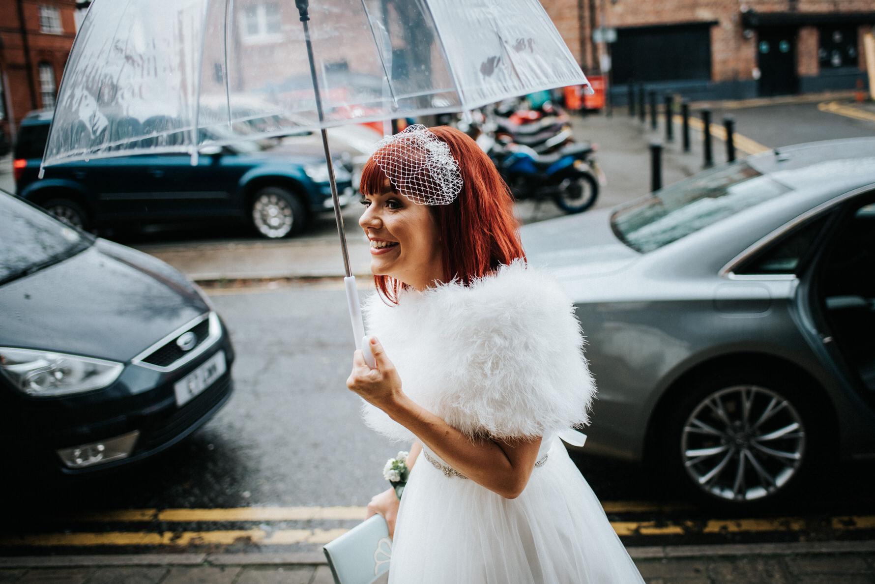 Cheshire Wedding Photojournalism bride with umbrella on way to ceremony