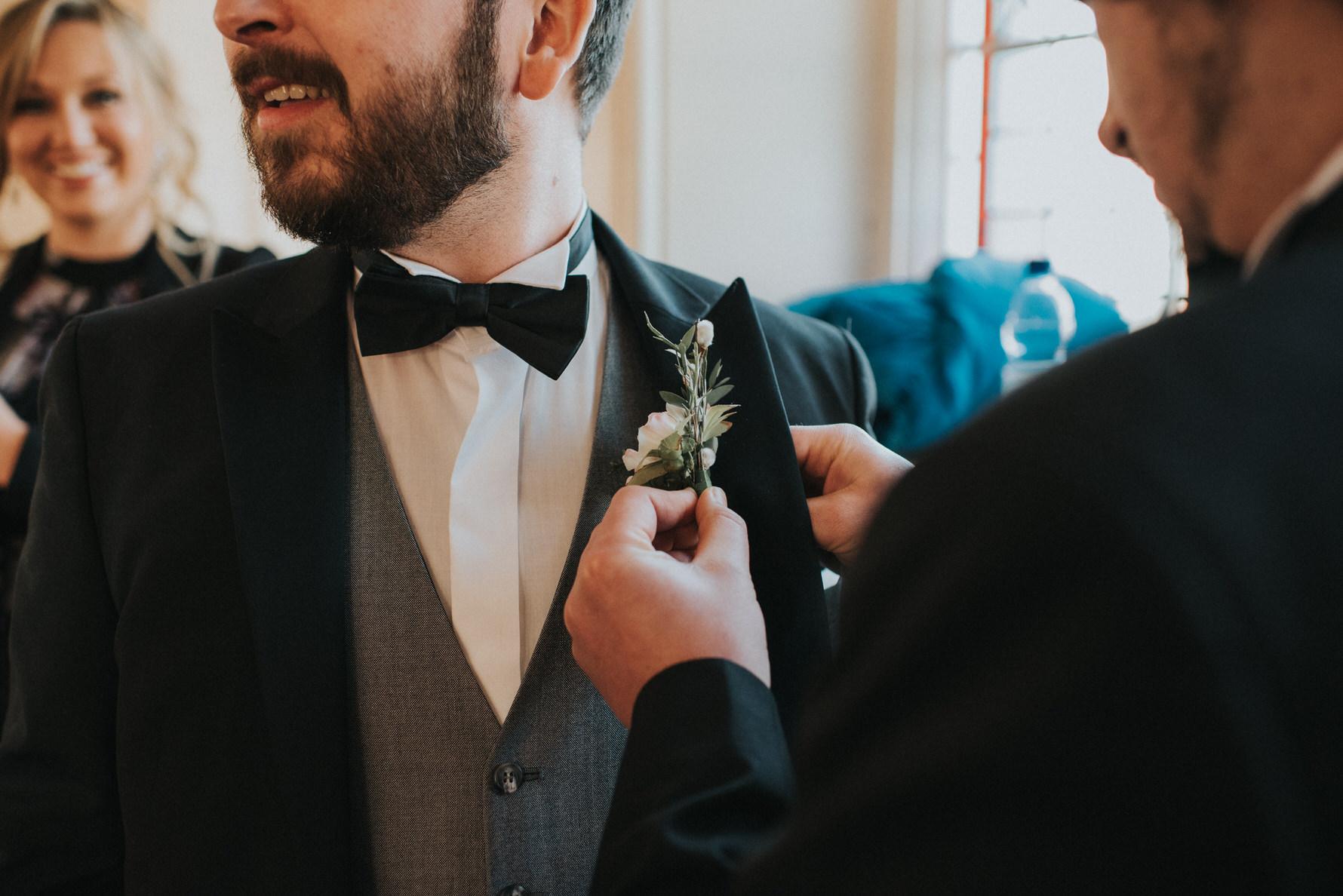 Wedding Photojournalism - Groomsman putting buttonhole on groom