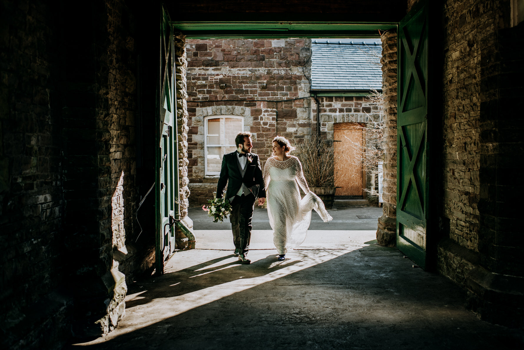 Wedding Photojournalism - A bride and groom walking through an archway