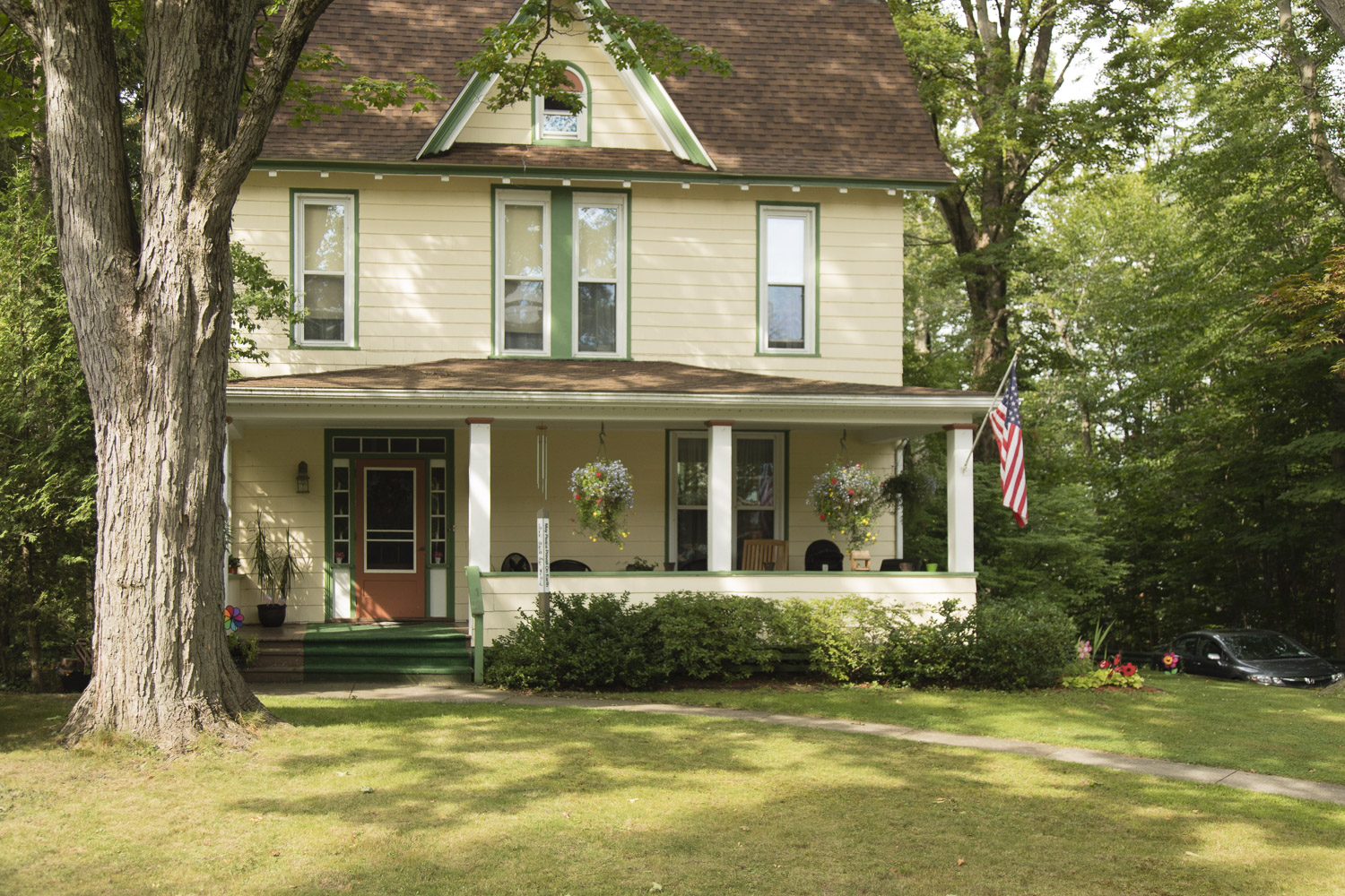 One of many way too cute for words houses. Chautauqua homes feature porches, lots of them, gingerbread, and flowers! AmericanFlags too!