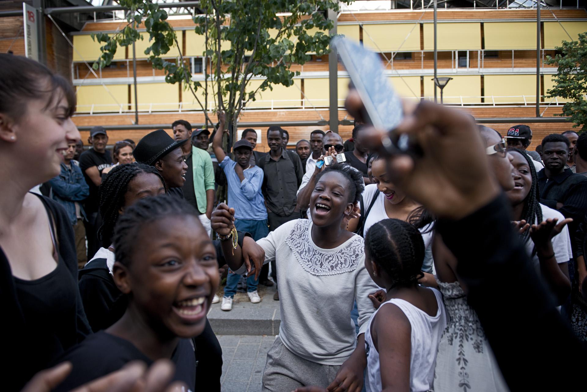Pour soutenir les migrants, des jeunes du quartier passe sur le campement avec une enceinte branché sur leur portable. Ils dansent et invitent les migrants à faire de même pour oublier l'espace d'un instant la dureté de leur quotidien. Paris 18ème,  le 27 juin 2015.