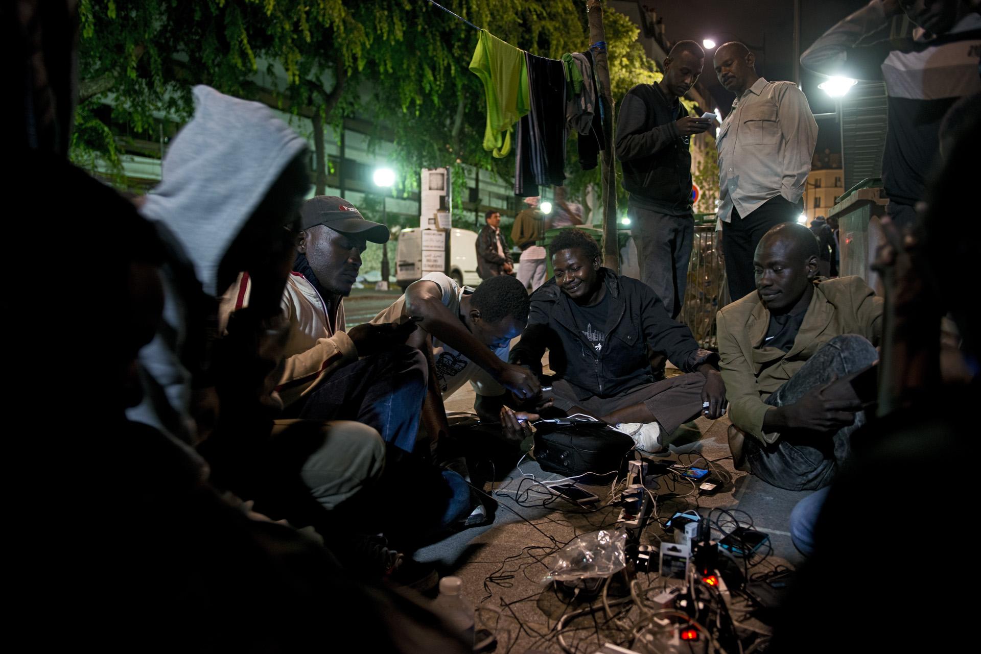 Sur le campement, comme partout sur la route de l'exil, les téléphones portables sont le seul lien avec le pays et la famille. Un riverain solidaire a bricolé un système de recharge à partir d'une batterie qu'il met à disposition tous les soirs.Paris 18ème, le 7 juillet 2015.