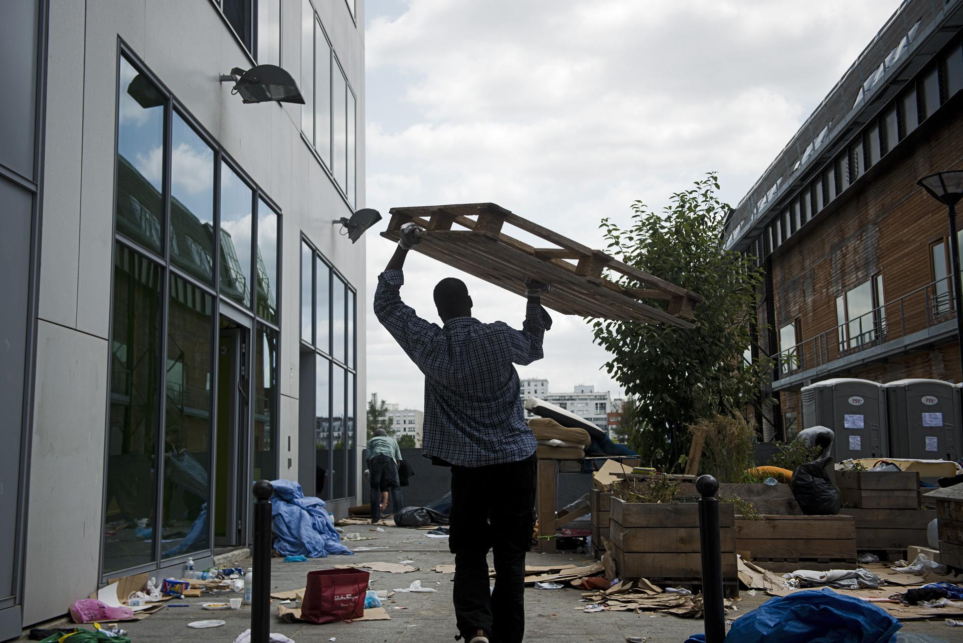 En vue de l'évacuation du campement, des soutiens mettent à l'abri les matelas et les palettes avant le passage des services de nettoyage de la ville de Paris qui embarquent tout sur leur passage.Paris 18ème, le 9 juillet 2015.
