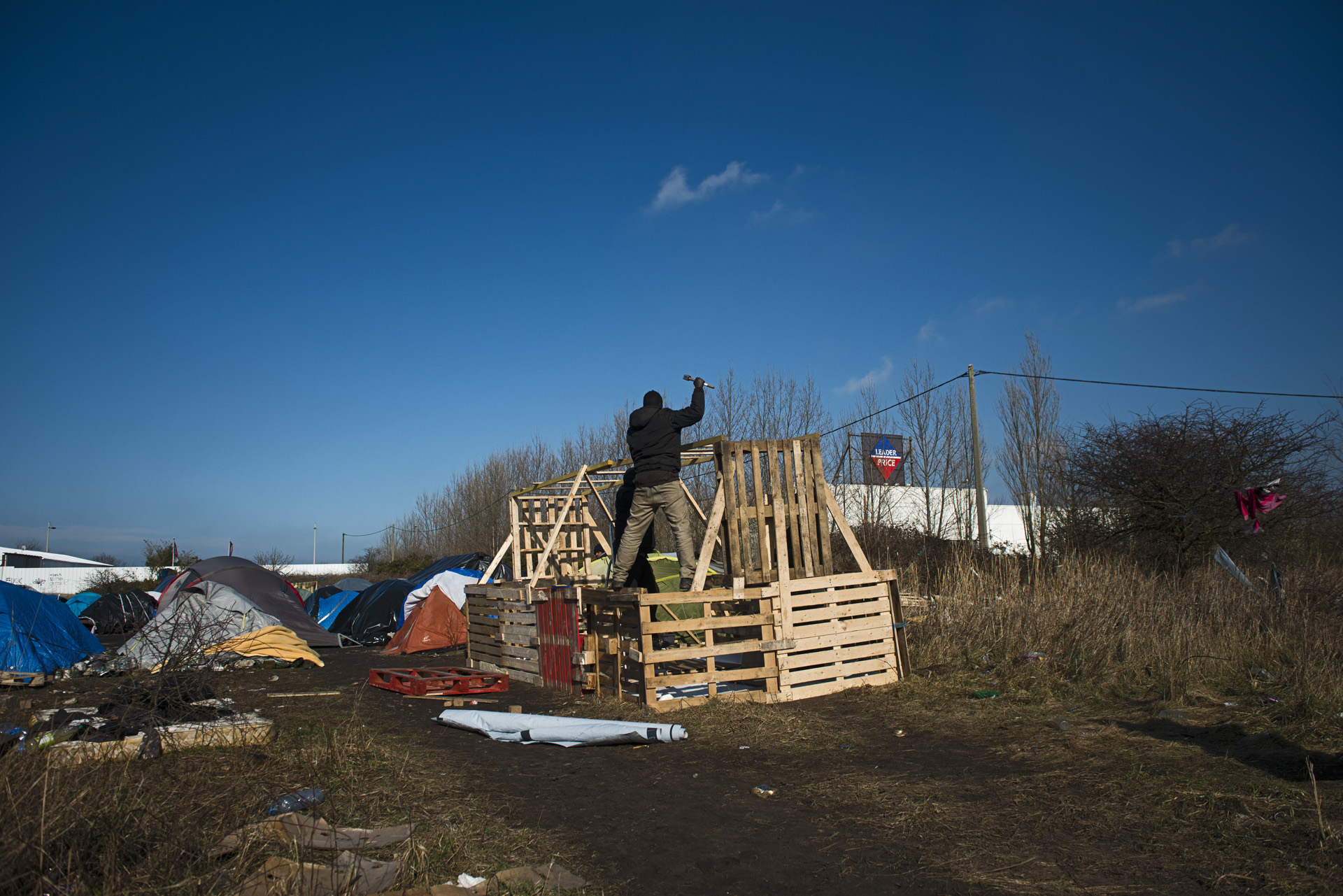 « Camp des Soudanais ».  A la périphérie de Calais, en contre-bas de l'autoroute où transitent les camions en partance pour l'Angleterre, des dizaines de Soudanais se sont installés au plus près d'un potentiel point de passage pour l'eldorado rêvé. L'attente dure souvent plusieurs mois. L'association Médecins du Monde (MDM) fournit des matériaux de base pour permettre aux migrants de construire des abris résistants à la pluie et au froid.  d