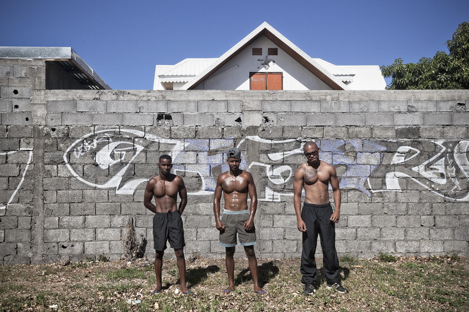 """Quartier """"Tintan"""", Le Port. Logan et ses amis font leur sport du matin. Ils habitent un des quartiers les plus sensibles de l'île. Sans emploi pour le moment, ils vivent de petits boulots et « profitent de la vie » comme ils disent. La pauvreté n'a ici aussi pas de couleur : Logan, à gauche, est d'origine Malbar, ses amis sont, pour l'un comorien et l'autre a des origines malgaches et africaines."""