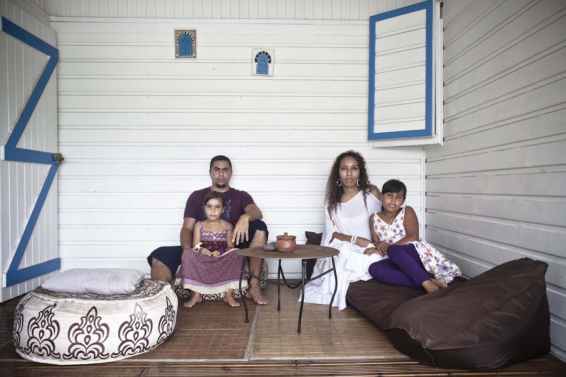 """Tampon, Ile de la Réunion. Janiver 2013.La famille Khlifi-Ethève devant leur maison. Mme Khlifi-Ethève est originaire de Tunisie. Elle est avocate et a grandi en France métropolitaine. Son mari, M. Ethève, est réunionnais (yab-créole). Il a quitté son île natale à l'âge de 3 ans pour aller en métropole. D'une famille catholique pratiquante, il s'est converti à l'islam en 2001. Il a toujours été en quête spirituelle et c'est avec l'islam qu'il dit avoir trouvé des réponses. Toute la famille a aujourd'hui quitté la France pour rejoindre la Réunion dans un but de retour aux sources mais aussi avec l'objectif de pratiquer l'islam librement sur une île qui, comme ils disent : """"accepte les différence de cultes de chacun"""". Ils sont également tous les deux membres de l'Association des Maghrébins de l'Ile de la Réunion (AMIR). Celle-ci a pour objet la création et maintien des liens de solidarité et de fraternité entre les maghrébins et leurs amis de l'île de la Réunion, ainsi que de promouvoir la culture et l'histoire du monde arabomusulman et l'organisation d'actions dans le domaine de l'éducation et de la formation."""