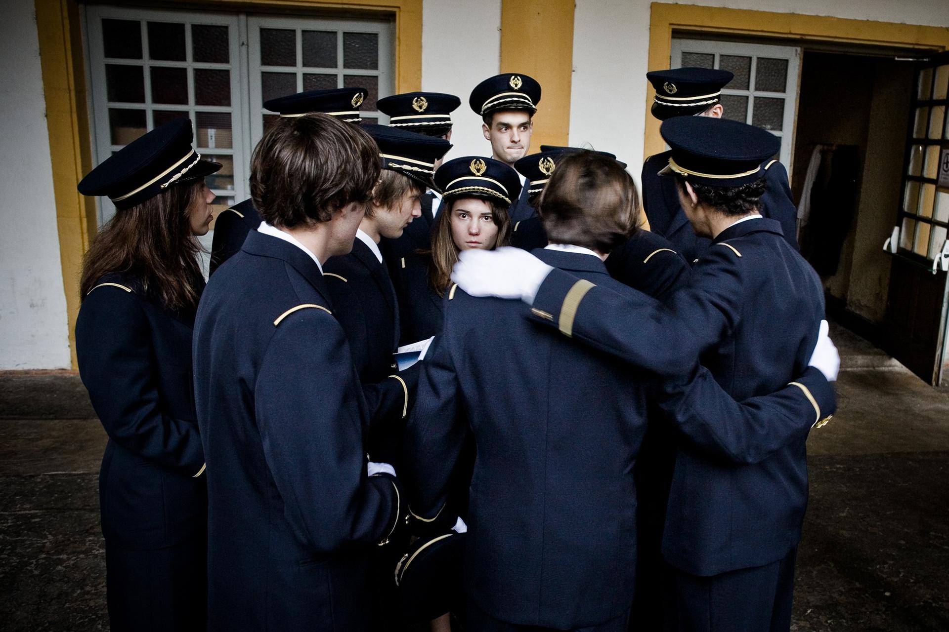 Un groupe de conscrits se concertent avant d'entrer dans le cloitre de l'abbaye où ils devront défiler devant leurs parents venus assister au baptême. Centre d'enseignement de Cluny, 2010.