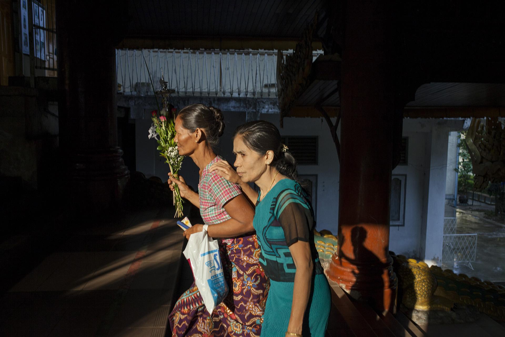 """Deux femmes montent les grands escaliers pour accéder à la pagode Shwe Dagon. Le bouquet de feuilles servira à faire des offrandes sur l'un des """"autels"""". Les offrandes servent entre autres à garder la chance de son côté, ou à éviter certains malheurs. Rangoun, Birmanie, Mai 2015."""