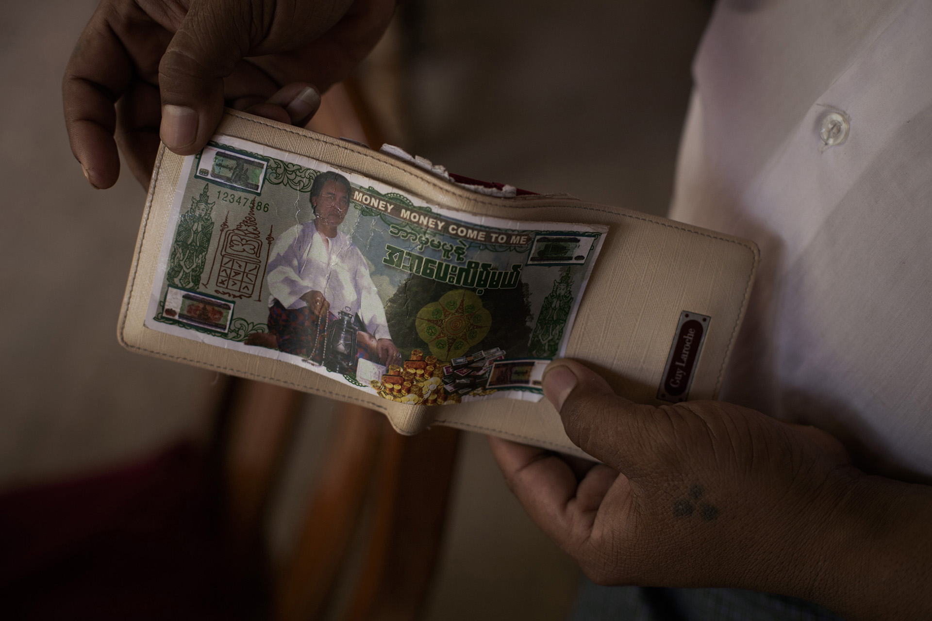 """Un serveur exhibant le billet porte bonheur qu'il a eu chez Kaung Si Thu, un astrologue réputé de Bagan. Sur ce faux billet on lit notamment """"Money, money come to me"""". Bagan, Birmanie, Mai 2015."""