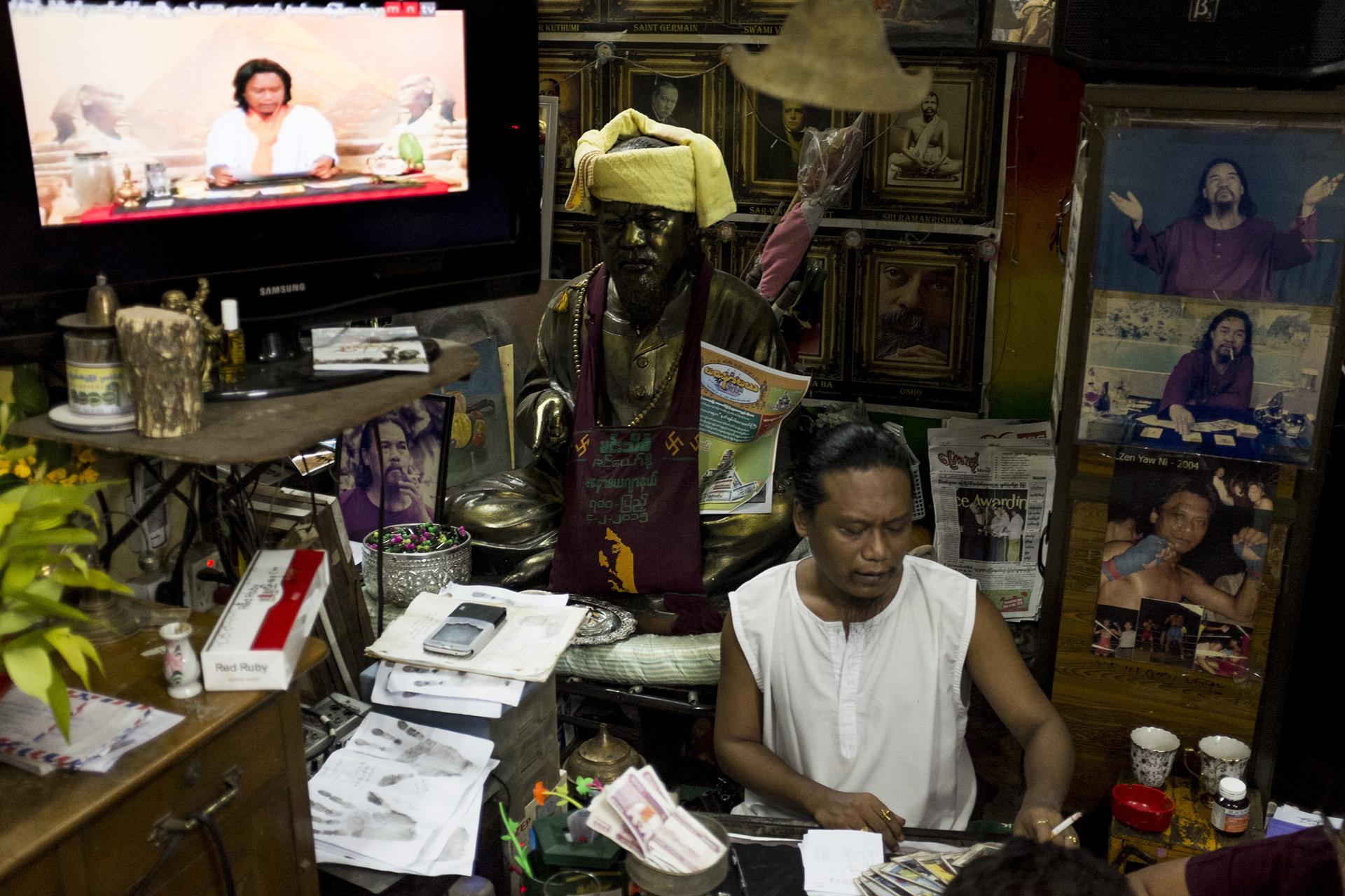 Zin Yaw Ni est un des astrologues les plus réputés du pays. Il a son émission à la télévision qui tourne en boucle dans son cabinet. Il forme également de futurs astrologues au métier. Rangoun, Birmanie, mai 2015.