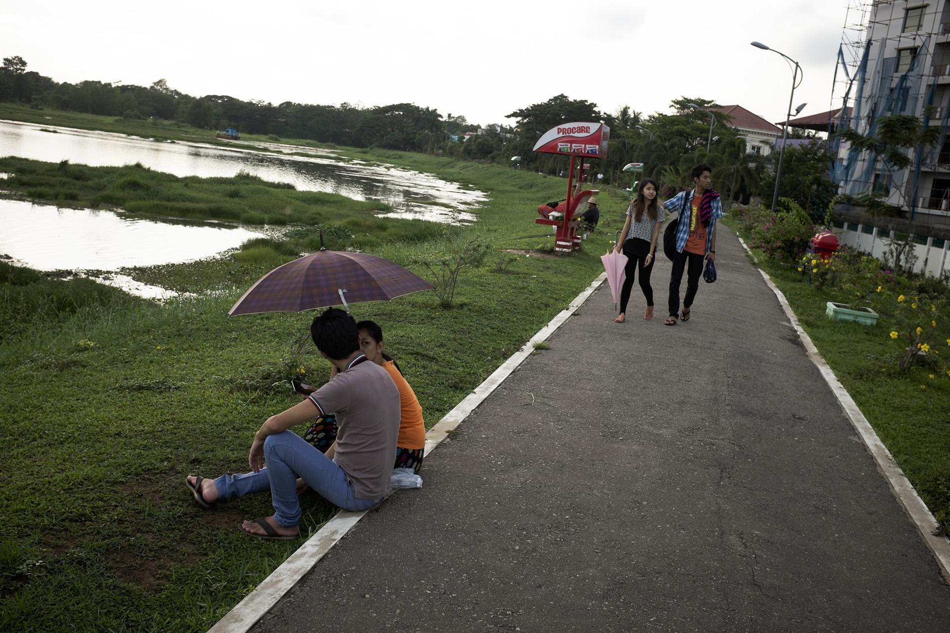 Retour à Rangoun sur le lac Inya. Ce lac situé à l'intérieur de la ville est un des lieux de rencontre fétiches pour les jeunes couples. Malgré l'ouverture sur l'extérieur, les mentalités changent doucement dans le pays et il est difficile d'assumer une relation avant le mariage. Birmanie, Mai 2015.