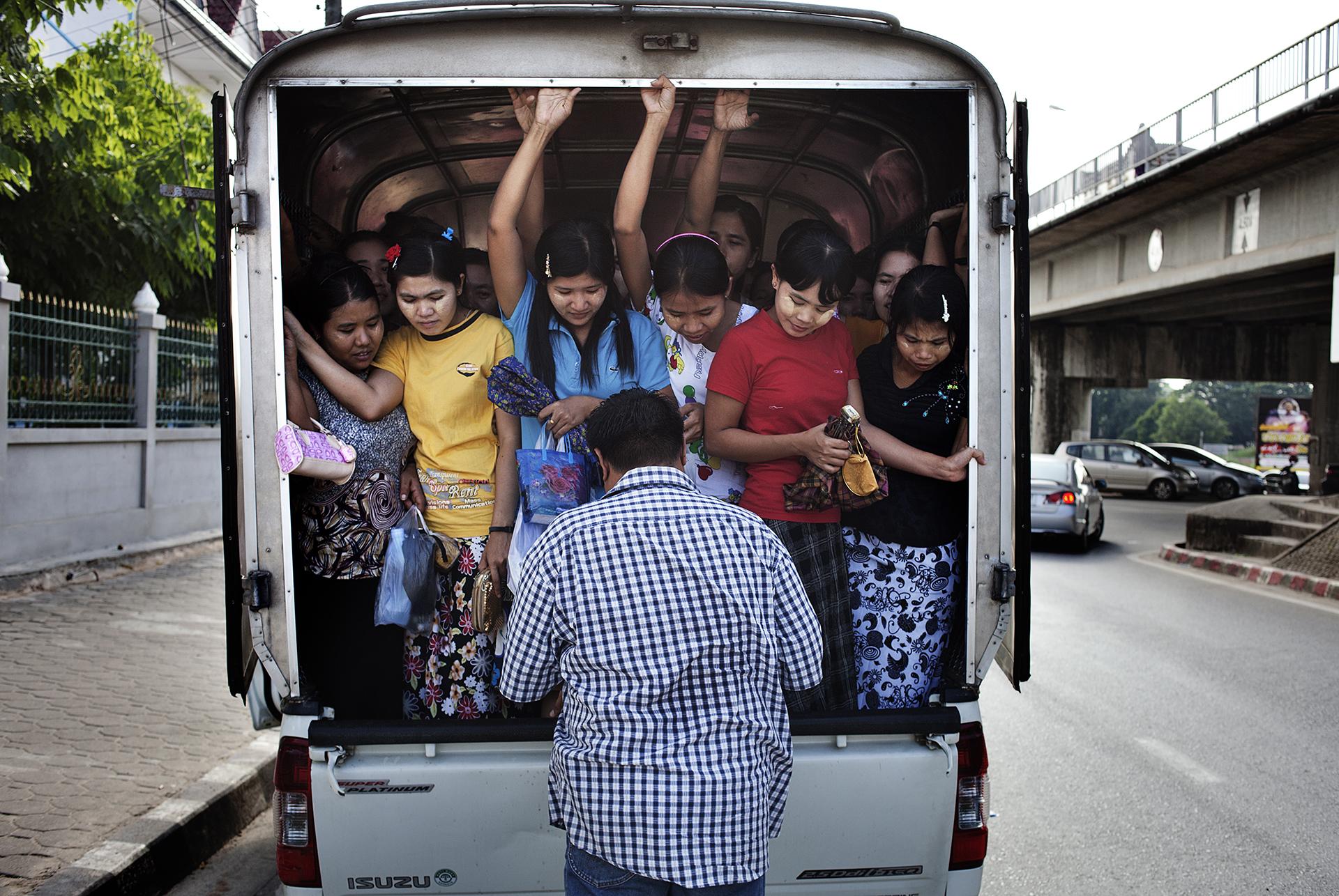 Des femmes sont emmenées à l'usine par un contremaître thaïlandais. Elles viennent de traverser la frontière et de renouveler leurs permis de travail. Leurs passeports sont confisqués par les gérants de l'usine. Poste frontière du pont de l'amitié, Province de Tak, Thaïlande, novembre 2013A Thai man fetches Burmese women in front of the thai custom office to bring them up for work in a factory, located in the nearby town, Mae Sot.Burmese are often employed as cheap labor in Thailand. Absence of rights lead to a high risk of extortion, arbitrary detention, forced labour and physical abuses. Border checkpoint Friendship bridge, Thailand. November 2013