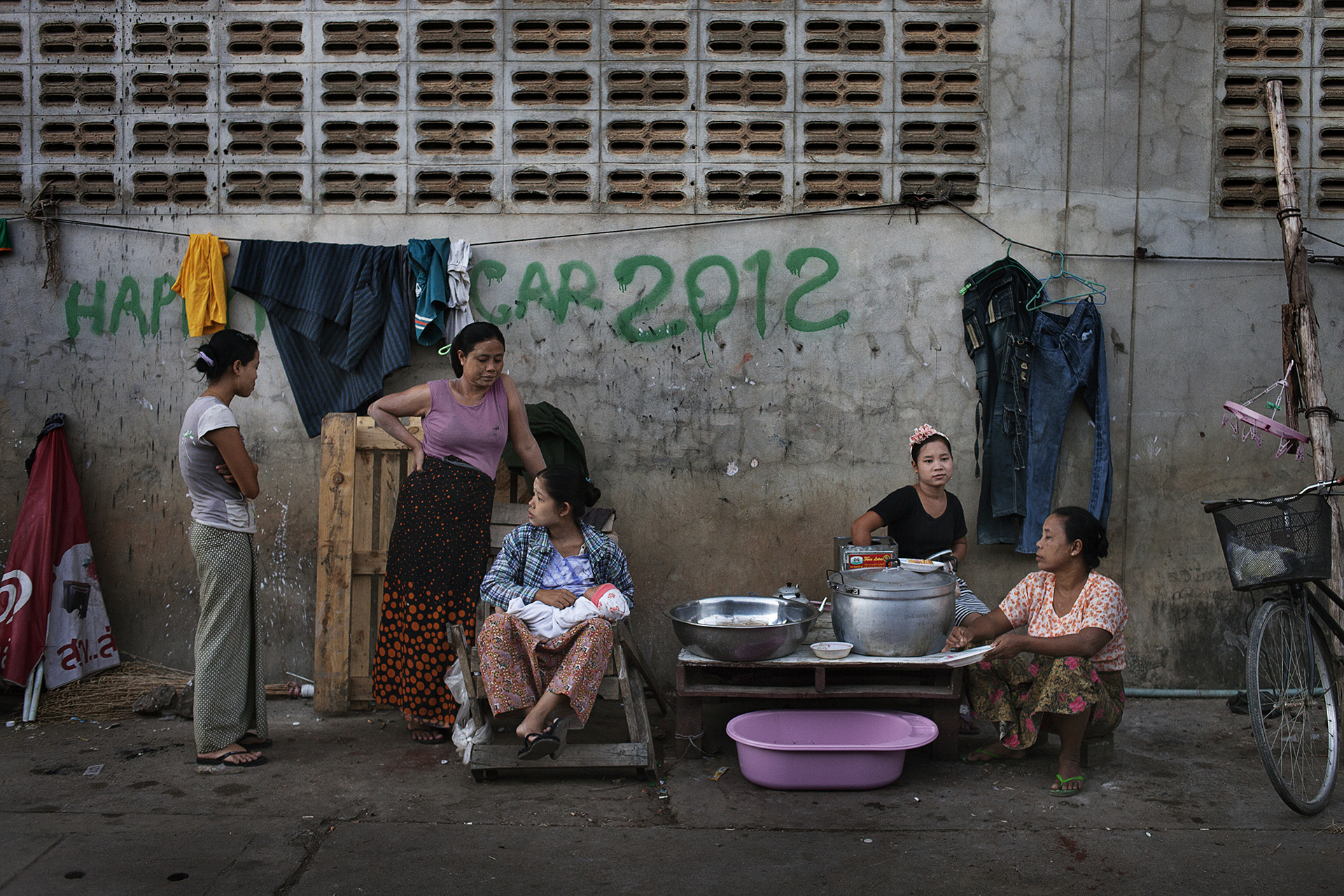Des jeunes femmes pendant leur pause dans l'usine qui les emploie. Ces ouvrières travaillent 12 heures par jour en moyenne, 7 jours sur 7. Ces usines emploient exclusivement des Birmans. Mae Sot, Thaïlande, novembre 2013Migrant workers in Mae Sot have a break at the factory they work in. They work 12 hours per day, and seven days a week.Burmese are often employed as cheap labor in Thailand. Absence of rights lead to a high risk of extortion, arbitrary detention, forced labour and physical abuses.