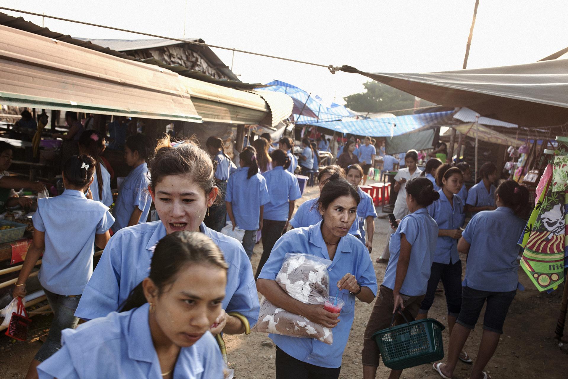 Des ouvrières font le marché pendant leur pause à quelques mètres de leur usine. La province de Tak est une «zone économique spéciale», où le droit du travail est rarement respecté envers les travailleurs birmans. Les entreprises thaïes jouissent entre autres d'avantages fiscaux pour s'implanter dans la province.Mae Sot, Thaïlande, octobre 2014