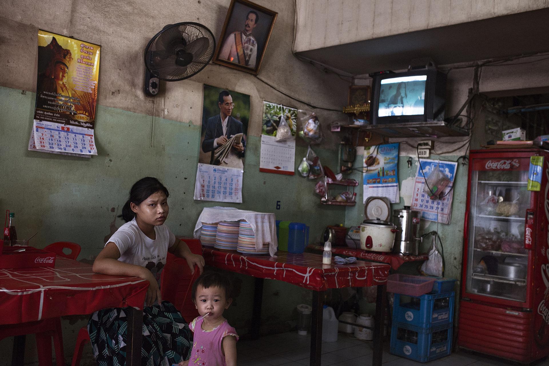 Une jeune fille birmane employée par une famille de Thaïlandais dans un restaurant du centre ville. Les jeunes filles servent souvent de domestiques dans les foyers ou restaurants thaïlandais.Mae Sot, Thaïlande, septembre 2014