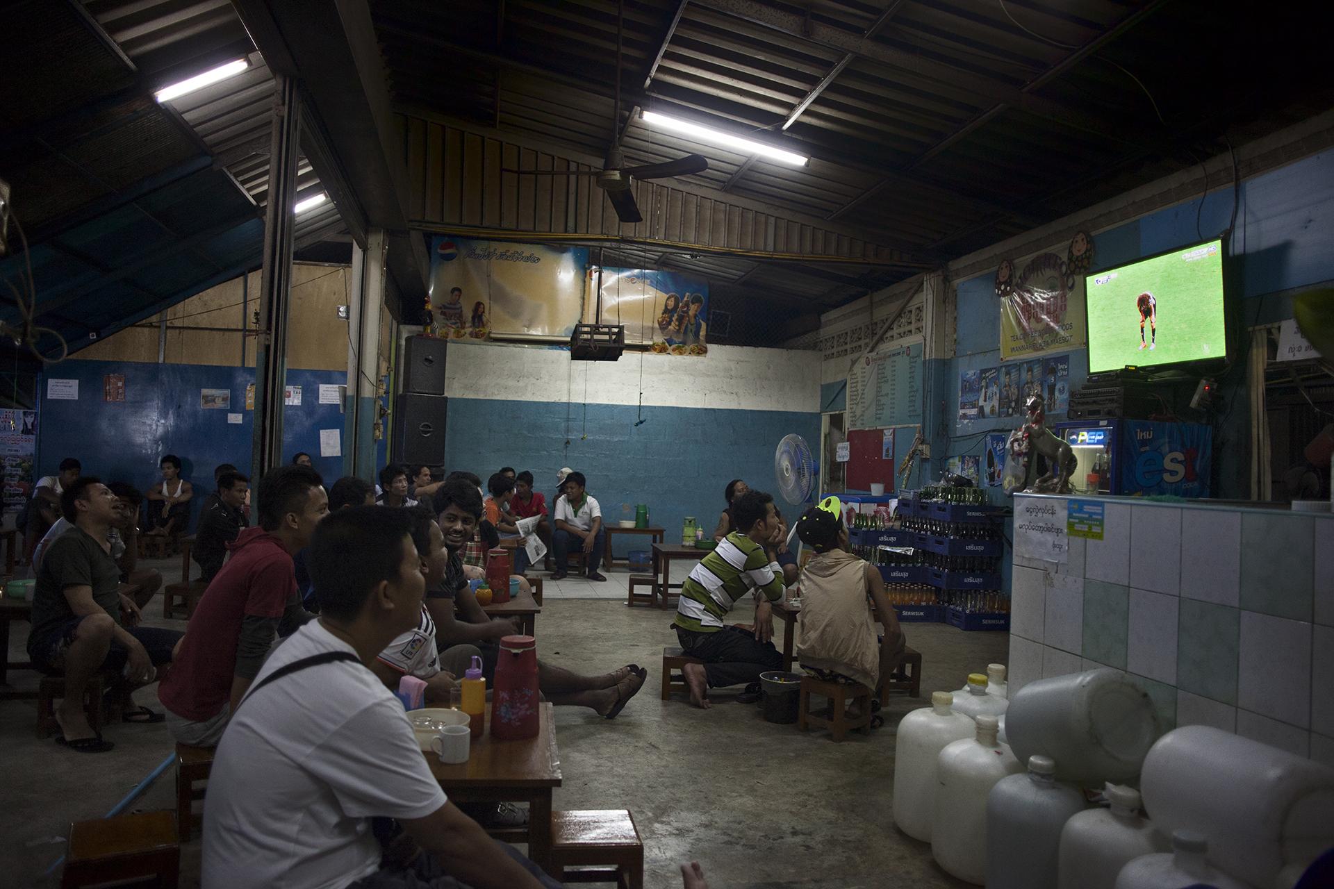 Soir de match au «Pho Too» tea shop. Ce café, l'un des plus grands de la ville est un lieu exclusivement birman. Les tea shops sont des lieux de socialisation importants pour la communauté. Mae Sot, Thaïlande, novembre 2014