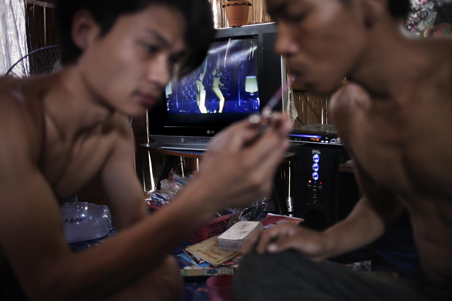 Des jeunes hommes fument du yaba dans une hutte du camp de réfugiés de Mae La. Cette substance de synthèse est produite en Birmanie et est composée de méthaamphétamine et de caféine. Cette drogue très addictive fait des ravages en Asie du sud-est et particulièrement en Birmanie et Thaïlande. La plupart des prostituées l'utilisent pour mieux supporter leurs conditions de travail. Camp de réfugiés de Mae La, Thaïlande, octobre 2013Young guys are smoking Yaba a local methanphetamine based drug. This drug is commonly used by sexworkers as well.Mae La camp, thailand. October 2013.