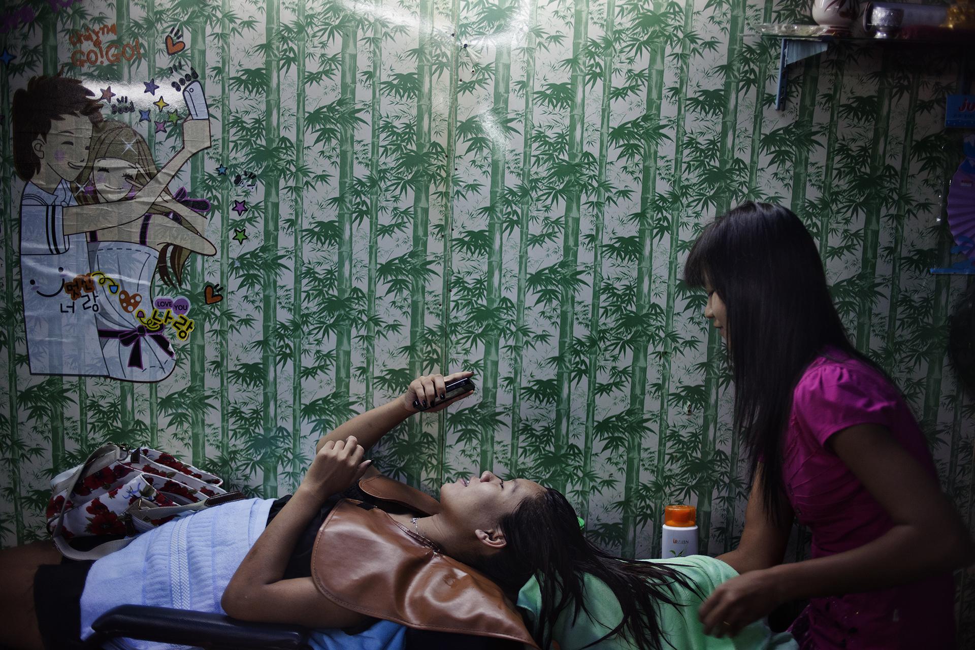 Phan, 17 ans, chez le coiffeur avant de partir travailler au karaoké bar. Elle a passé 7 ans dans un camp de réfugiés et est venue à Mae Sot dans l'espoir d'intégrer l'université thaïlandaise. Néanmoins l'université coûte trop chère et elle a fini par accepter un job d'hôtesse dans un karaoké bar. Mae Sot, Thaïlande, novembre 2013Phan, 17 years old is getting ready in the hairdresser before going at work in the Karaoke bar where she is employed. She came to Mae Sot with the hope to integrate a Thaï university, but lack of money forced her to start her job as a hostess. Mae Sot, Thailand. November 2013.