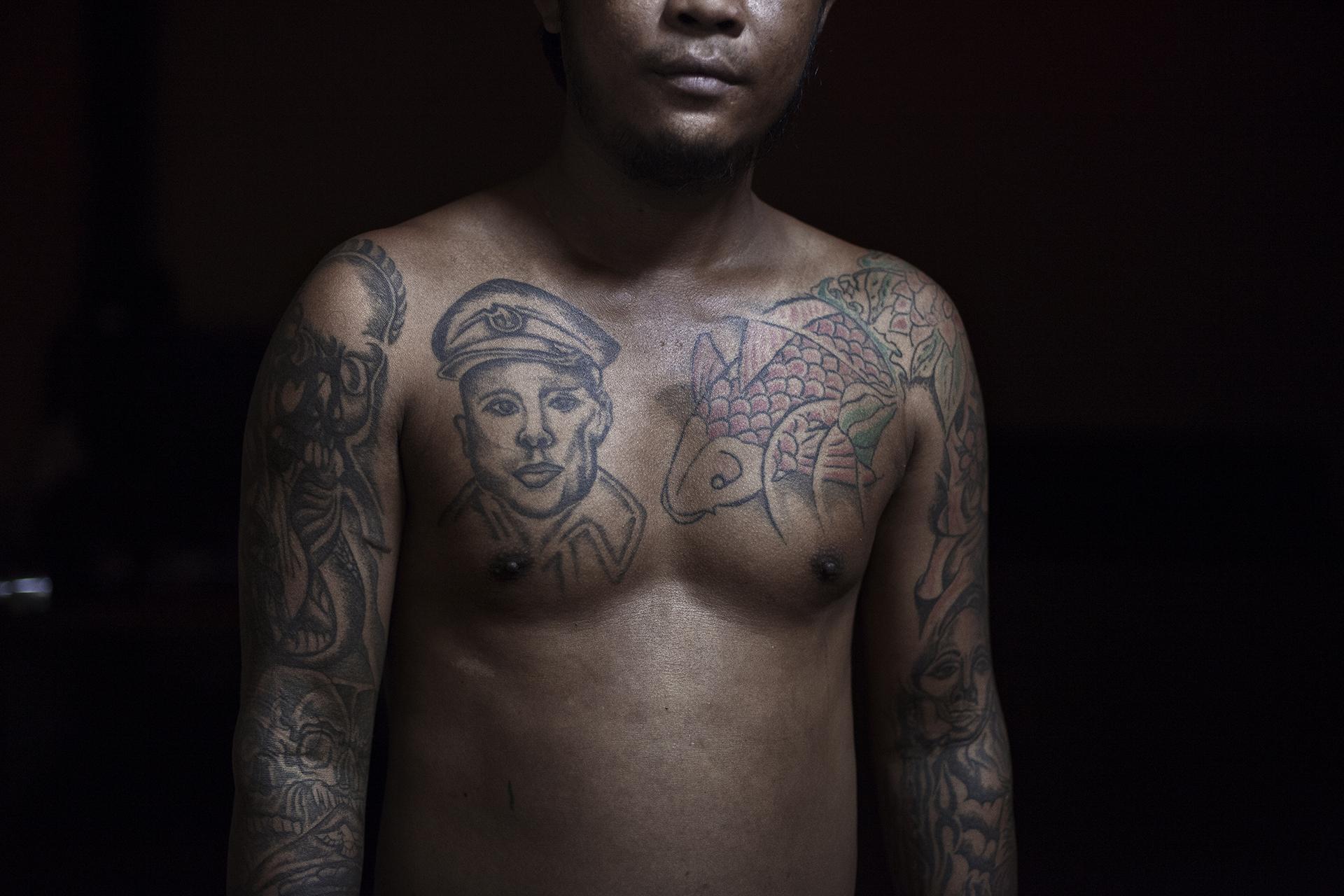 Un mac birman prend la pose dans le bordel qu'il gère pour le compte d'un Thaïlandais. Sur son torse est tatoué le portrait du général Aung San, le père de Aung San Suu Kyi. Grand artisan de l'indépendance, ce dernier a été assassiné le 19 juillet 1947. Il est une figure emblématique pour les Birmans.Mae Sot, Thaïlande, octobre 2014