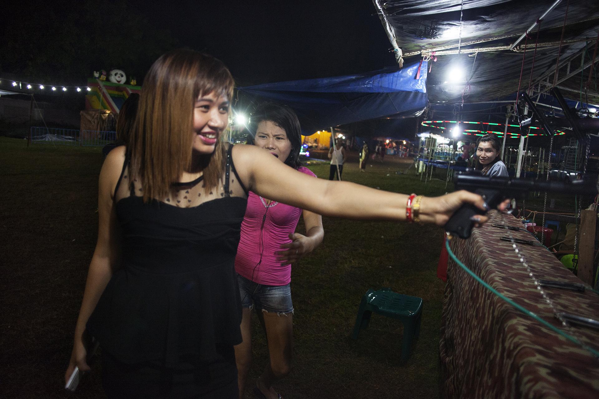 Nay Ji, 26 ans, s'amuse avec une de ses amies dans la kermesse organisée à l'occasion du festival bouddhiste Loy Kratong.La plupart des prostituées évitent les marchés, les restaurants, par peur des regards. Elles sont stigmatisées dans la culture birmane et sont très isolées. Mae Sot, Thaïlande, 2014