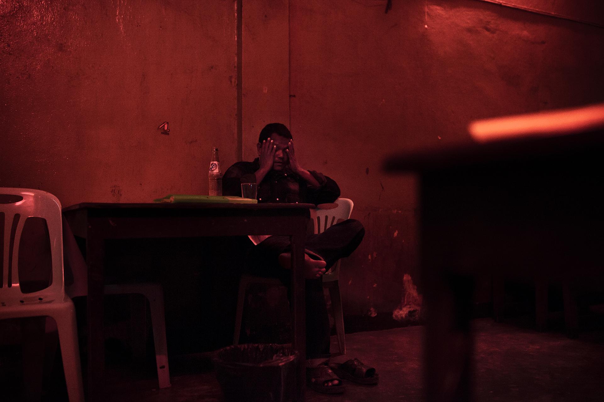 Un homme dans le bar d'un des bordels de la ville. Dans ce lieu, les clients paient 300 bahts (7€) pour passer une heure avec une fille. Mae Sot, Thaïlande, novembre 2014