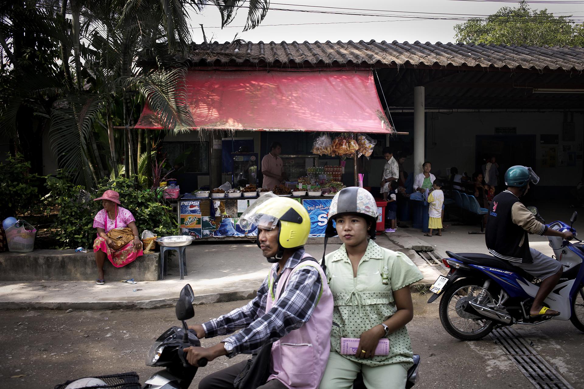 Entrée de la clinique Mae Tao. Elle a été fondée il y a 25 ans par le docteur Cynthia Maung en collaboration avec la Karen National Union. Aujourd'hui la clinique Mae Tao est l'un des seuls lieux d'accès aux soins pour les Birmans. Chaque année, plus de 150 000 patients bénéficient de soins gratuits, dont plus de la moitié viennent spécialement de Birmanie. Avec l'ouverture du pays, les sponsors de la clinique retirent petit à petit leurs fonds. Néanmoins, le besoin de soins n'a pas baissé dans la région. Mae Sot, Thaïlande, octobre 2013Mae Tao clinic offers free medical care to people from neighboring Burma populations. With 150 000 admissions per year and half from Myanmar they are a . With relative changes in Burma, their sponsors began to decrease their founds despite the fact that Burmeses migrants have built their lifes in this side of the border.