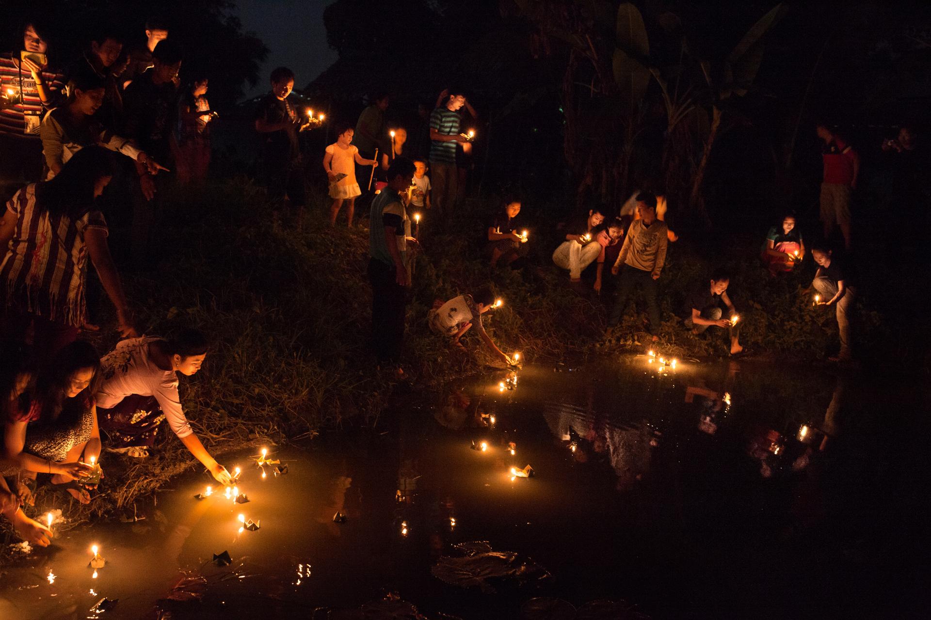 Des Birmans déposent des bougies sur l'eau d'une mare la nuit de Thadingyut. Cette date marque la fin du carême bouddhiste. Elle est l'occasion de festivités, de visites dans les temples et d'illuminations.Province de Tak, Thaïlande, octobre 2014