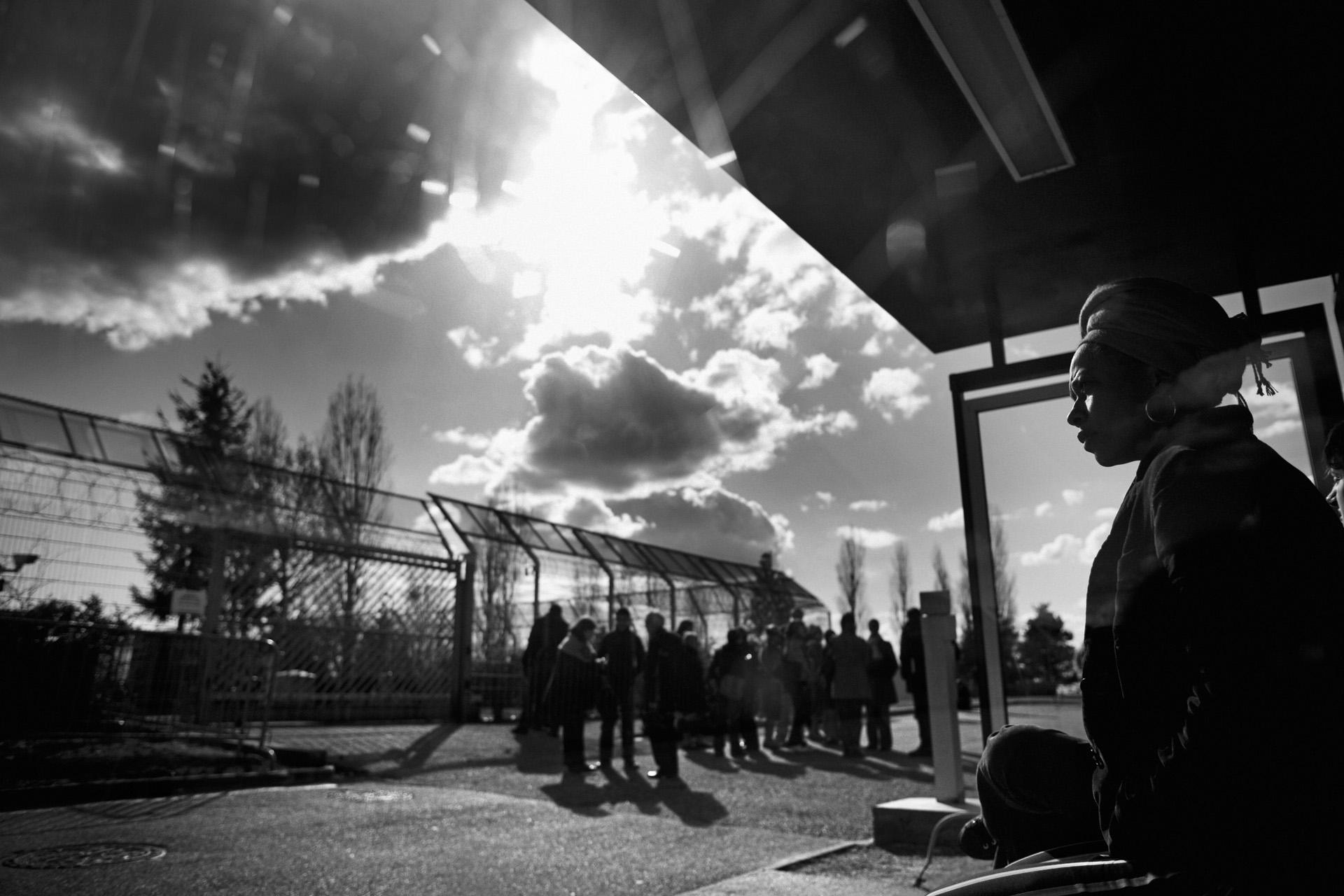 Lyon, le 4 avril 2010. Devant le centre de rétention Saint-Exupéry de Lyon, Florence attend pour voir Guilherme. Ce centre compte parmi ceux qui peuvent accueillir des familles. Les centres de rétention administrative (CRA) ont été officiellement créés le 29 octobre 1981. Ils ne dépendent pas de l'administration pénitentiaire. La privation de liberté n'a pas de caractère punitif lié à la décision d'une autorité judiciaire, elle est le résultat d'une décision administrative.