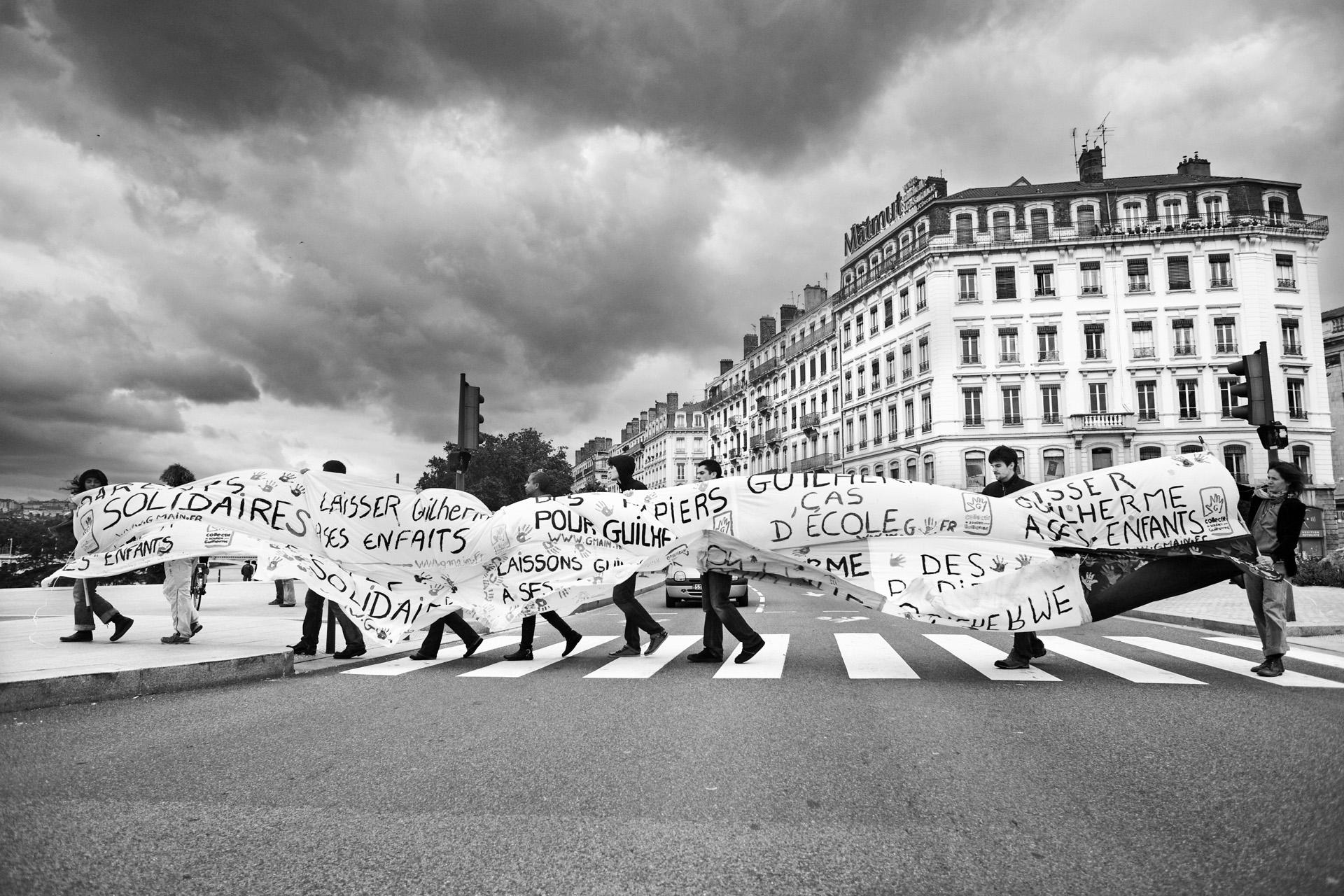 Lyon, le 20  juin 2010. Pour continuer à être visible, le collectif de soutien a fabriqué une banderole géante qu'il promène régulièrement dans les rues de Lyon et qu'il affiche à chaque événement culturel.