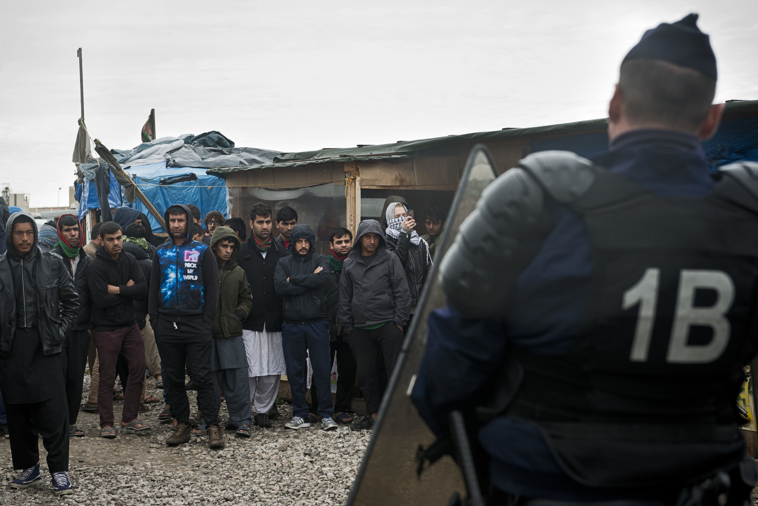 Pour l'instant, les forces de l'ordre restent positionnées à l'extérieur de la Jungle et procèdent uniquement à de brèves opérations à l'intérieur du camp, pour fermer les restaurants et les échoppes déclarées illégales ou pour encadrer des officiers de police judiciaire venus interroger et arrêter quatre jeunes Afghans soupçonnés d'être impliqués dans l'agression d'un journaliste et le viol de son interprète.  Les migrants observent ces incursions policières, silencieux et fatalistes.