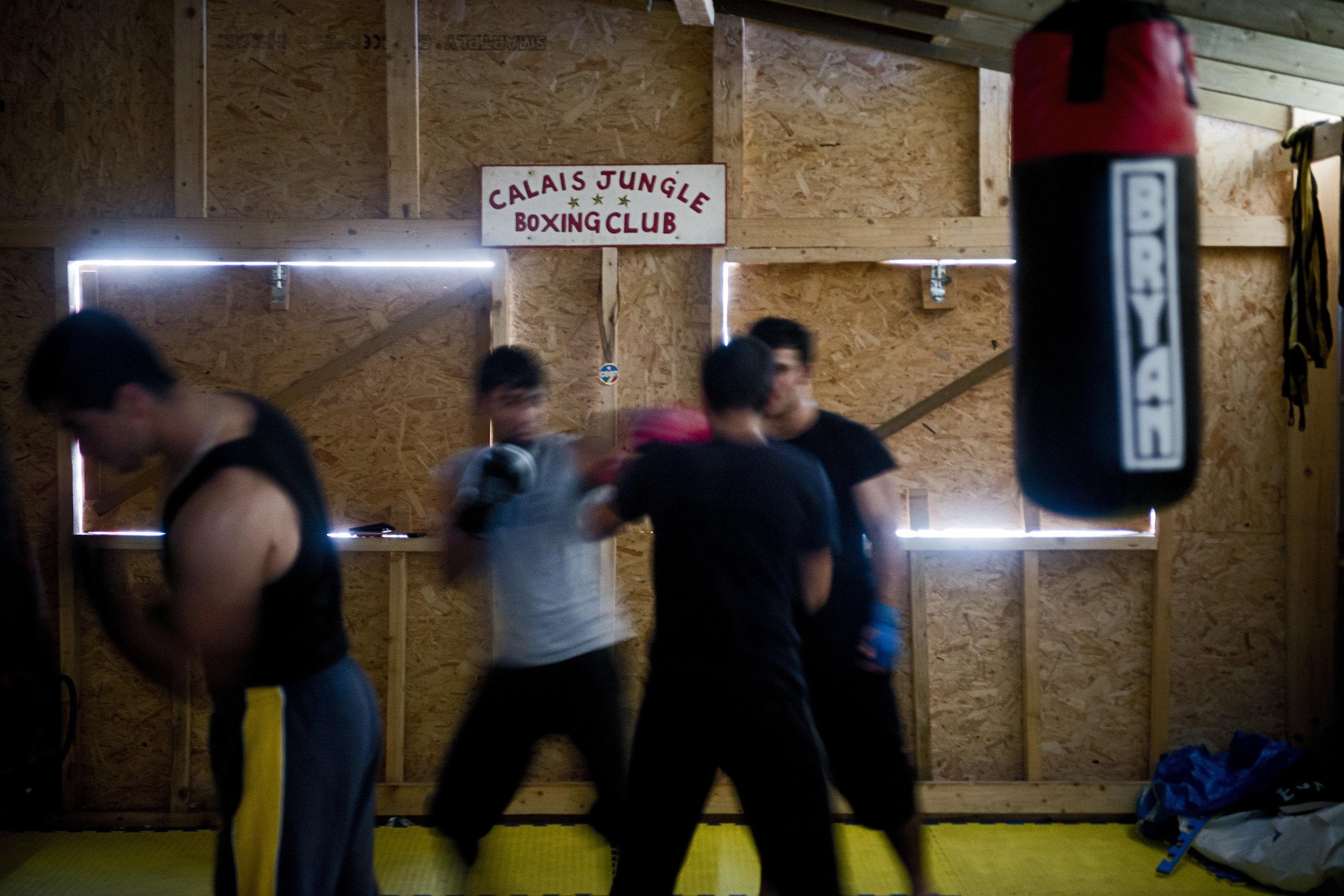 Pour tromper l'attente, des réfugiés afghans enchainent une série de pompes et de tractions. Dans les coups qu'ils portent au sac de sable, on sent la rage de l'impuissance.  Abdul qui a appris à boxer en Angleterre où il a vécu entre l'âge de 12 à 20 ans avant de se faire expulser, est l'une des réfugiés les plus assidus du Calais Jungle Boxing Club tenu par Josh, un bénévole Britannique originaire de Sheffield. D'habitude, à cette heure là, une vingtaine de personnes se pressent à l'entrainement. «Mais là, les gens sont trop préoccupés par la fermeture du camp pour venir» constate Josh. «A force de réfléchir quoi faire,ils ont la tête qui explose» confirme Abdul.