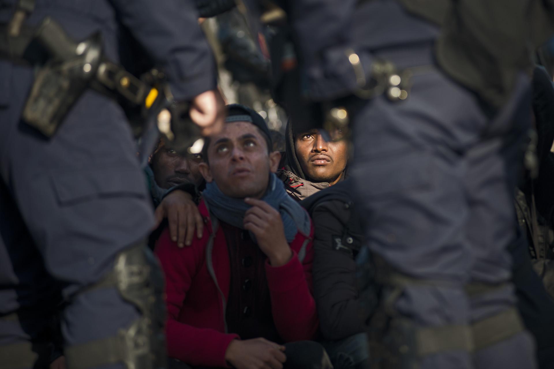 Calais. Devant le centre de répartition, la situation se complique. Des centaines de réfugiés se présentent devant la file prioritaire des mineurs. C'est la confusion la plus totale. De nombreux migrants, qui ne veulent pas demander l'asile ailleurs qu'en Angleterre, pensent qu'il suffit de se déclarer mineur pour pouvoir rejoindre légalement leur eldorado britannique grâce aux procédures de réunification familiale qui ont été accélérées. Le processus de répartition s'enraye, ce sont les premières bousculades et les premiers dérapages : « Bambino, yes ! Bambino, no ! » Les CRS et le personnel de France terre d'asile commencent à « trier au faciès », constatent les journalistes et les associations. Les réfugiés qui « ont visiblement l'air adulte » sont écartés sans autre façon et sans avoir de possibilité de recours.