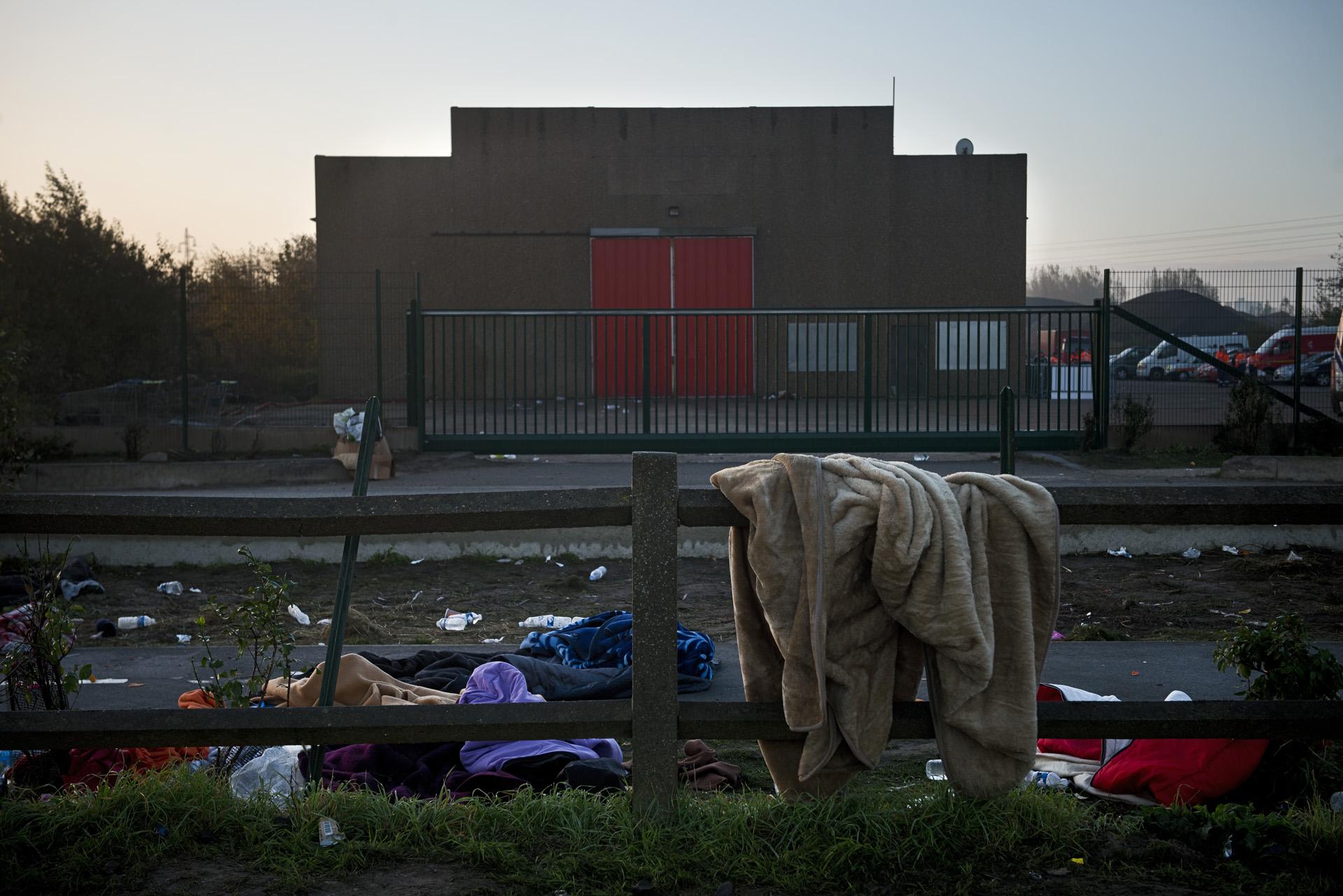 Calais, jeudi 27 octobre 2016. Le sas de répartition a fermé ses portes et est redevenu le hangar désaffecté qu'il était. Selon la préfecture, 5 596 réfugiés ont été « mis à l'abri » ; 4 500 ont été transportés dans les bus et répartis dans les différents CAO, 237 mineurs ont pu partir pour l'Angleterre, 1 500 autres ont rejoint les conteneurs du centre d'accueil provisoire en attendant d'être fixés sur leur sort. « La jungle, c'est fini ! », martèle depuis la veille la préfète Fabienne Buccio. Pourtant, dans la nuit de mercredi à jeudi, une centaine de personnes dorment devant le sas, sur le sol glacé, en espérant un hypothétique bus. Devant l'entrée du camp de containeurs fermé pour cause trop plein, ce sont des dizaines de mineurs enroulés dans de simples couvertures qui passent la nuit.