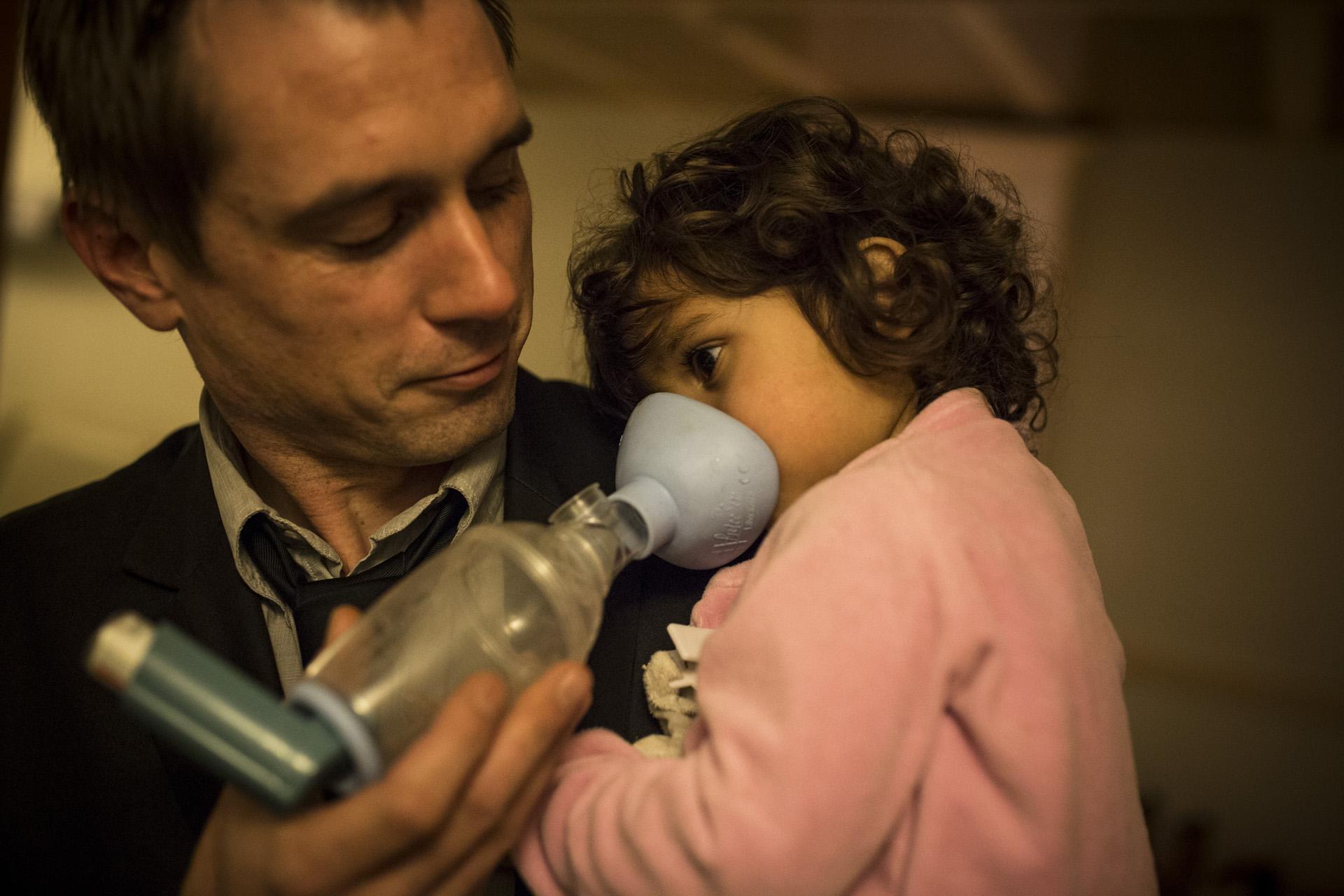 Alexandre Chignard du collectif Stop Pollutions et une de ses filles sous bronchodilatateur, dans leur maison voisine de l'usine d'Harsco Minerals. Imphy, décembre 2015.