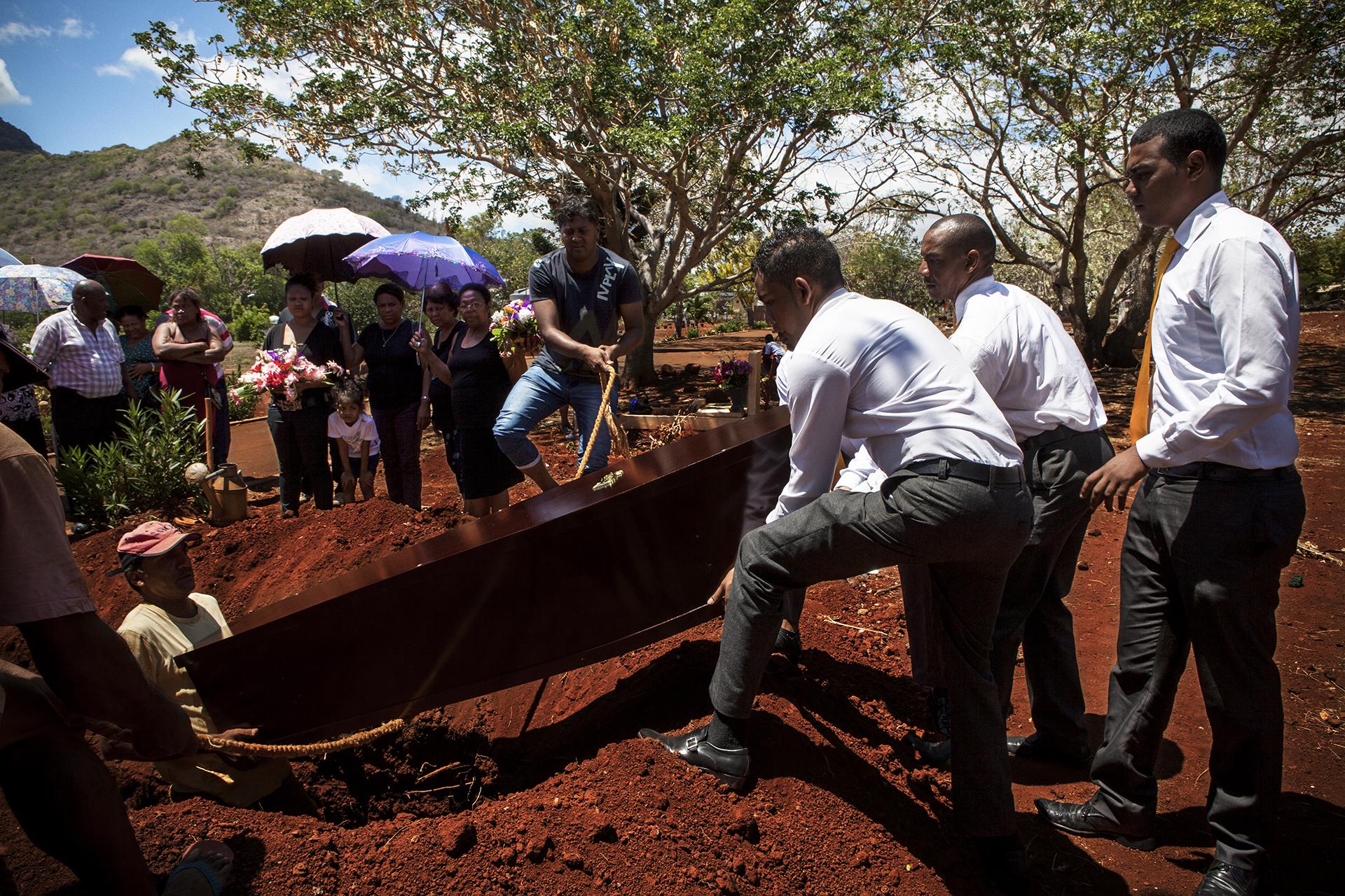 Le cimetière Muza est situé dans les hauteurs de Port Louis. Au pied de la montagne.L'assistance n'est pas très nombreuse pour l'enterrement d'Emilie Louise Codor, la doyenne des Chagossiens. Un simple trou creusé dans le sol, quelques membres de sa famille, Olivier Bancoult du Chagos Refugee Group… La sépulture n'est pas à la hauteur du symbole. « Un enterrement ça coûte cher, nous n'avions pas les moyens de faire plus… et la famille est éparpillée un peu partout, à l'étranger, beaucoup n'ont pas pu venir.. » nous dit son petit fils. Le trou sera simplement rebouché et quelques fleurs seront déposées. Pas de stèle. Pas de croix. Pas de nom. Emilienne reposera ici. Loin de sa terre natale. Du cimetière on ne voit pas la mer.