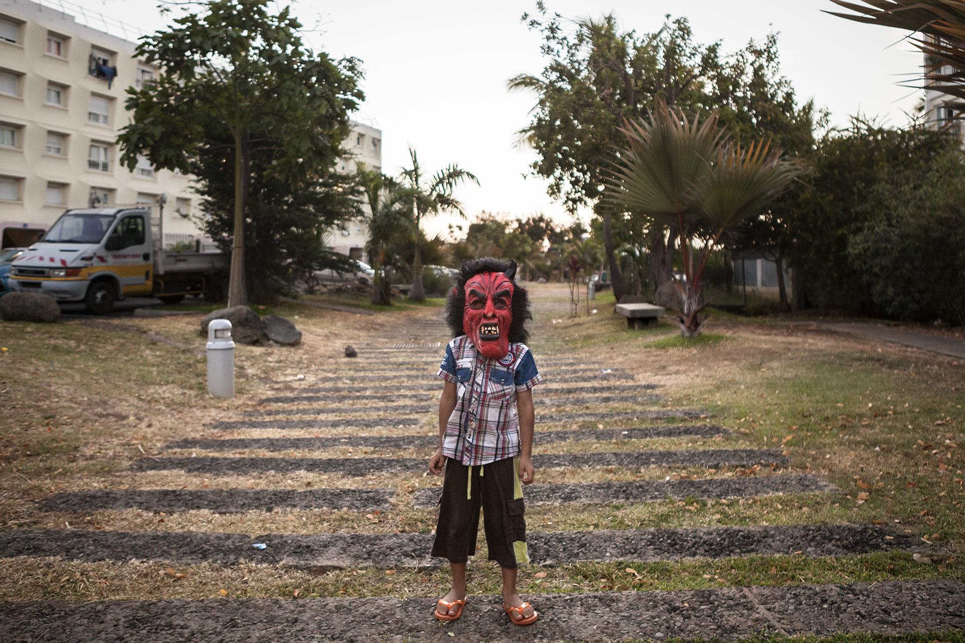 Fin d'après-midi dans un des quartiers de la ville. Un jeune s'amuse en bas de son immeuble avec un masque. La population portoise est à l'image de la population réunionnaise, elle augmente rapidement chaque année. Plus de 10 000 personnes par an. La raison principale est l'excédent des naissances sur les décès. Elle pourrait atteindre le million d'habitants à l'horizon 2030. C'est donc une population jeune, 41% des Réunionnais ont moins de 25 ans.