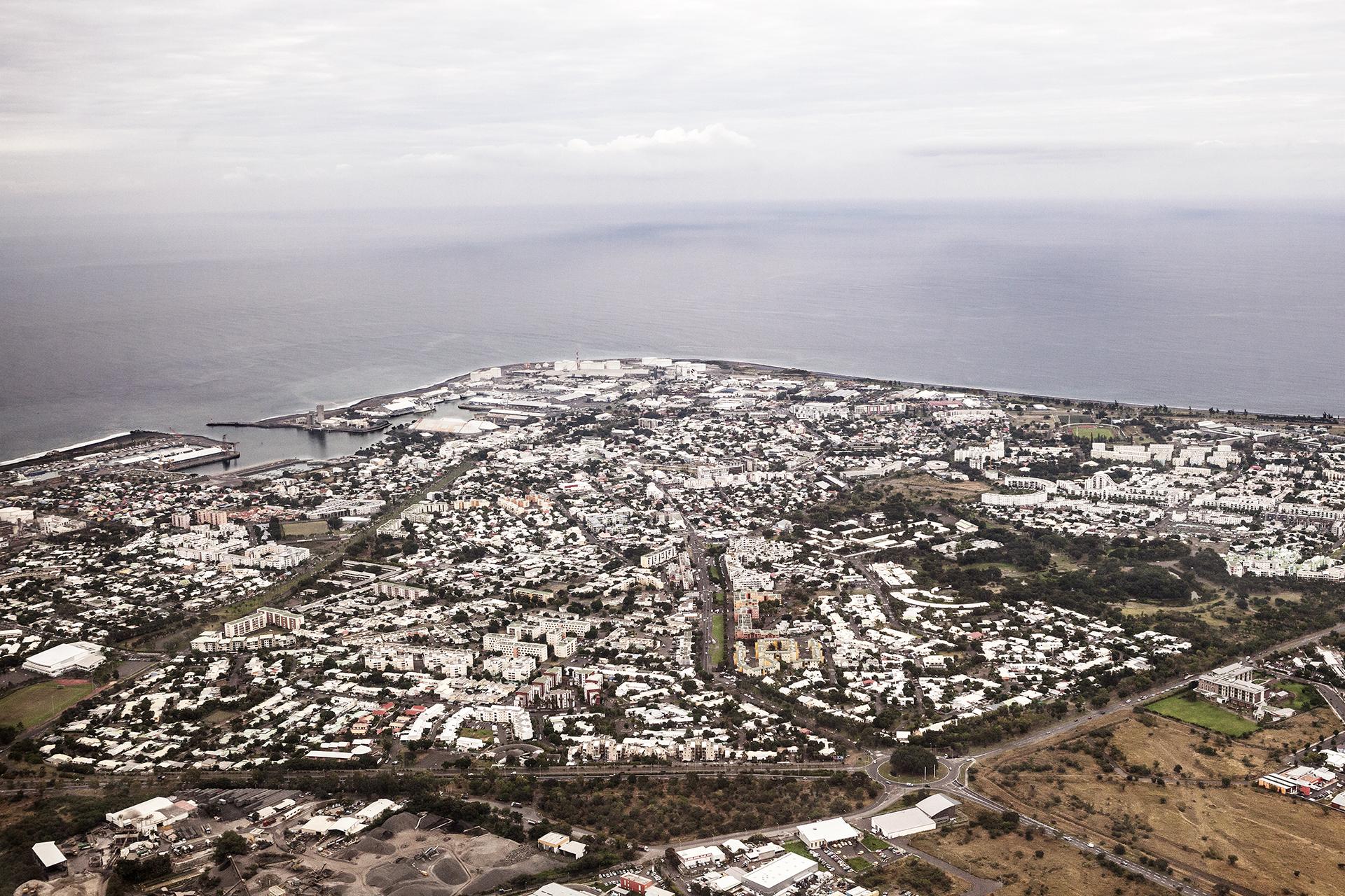 Le Port est sans doute le point le plus chaud de La Réunion. Arrachés au désert qui s'étend sur la pointe ouest de l'île, la ville et son port sont le centre stratégique du territoire. À la fois base navale, militaire, gare maritime, port de commerce, de pêche et de plaisance, le port de la Pointe des Galets est une plaque tournante historique pour les marchandises comme pour les populations qui ont formé le métissage de l'Île de la Réunion. Le passé industriel et populaire de la ville, sa culture prolétaire et cosmopolite, a forgé l'identité d'une population combative et fière de son histoire. Mais Le Port porte les stigmates de son héritage ouvrier. Dans cette ville composée à 80 % de quartiers HLM, les habitants subissent de plein fouet les problématiques économiques d'un département français où près de la moitié de la population vit sous le seuil de pauvreté.